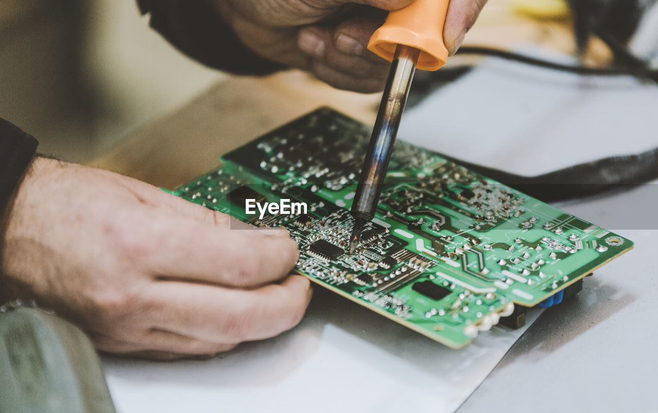 Cropped hands of engineer repairing mother board on table