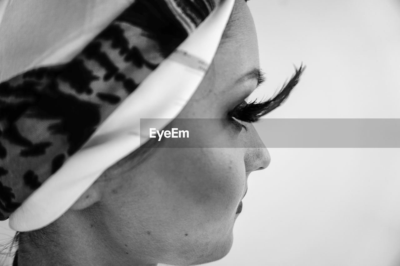 Profile view of young woman with false eyelash against white background