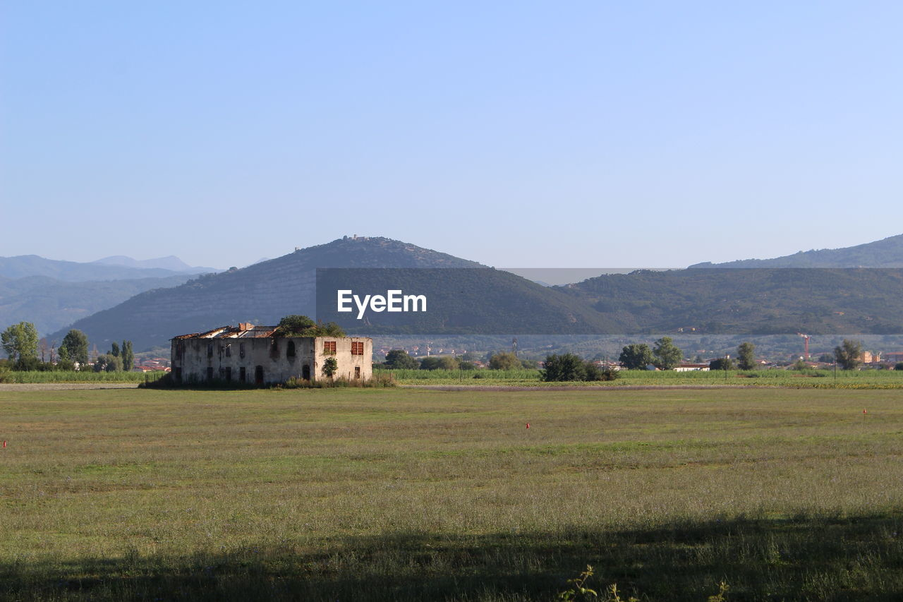 Houses On Field By Mountains Against Clear Sky