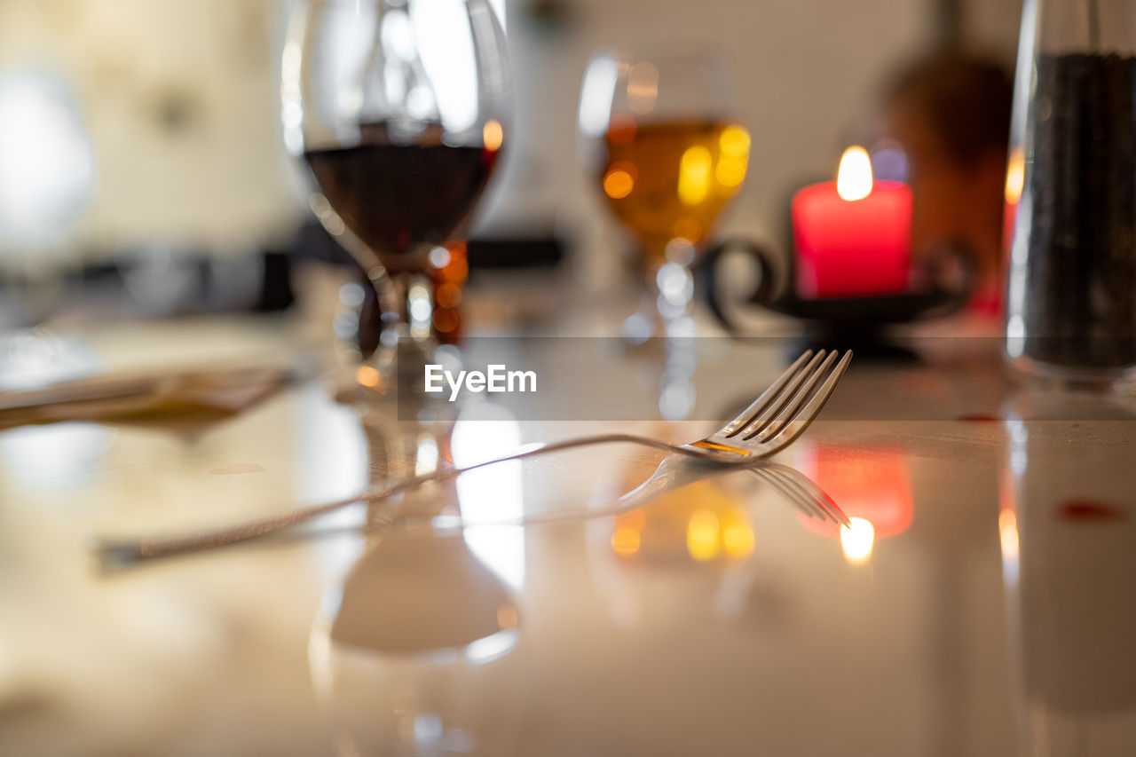 wineglass, alcohol, drink, refreshment, glass, wine, food and drink, table, indoors, glass - material, candle, selective focus, household equipment, kitchen utensil, red wine, bottle, fork, still life, drinking glass, food, no people, crockery, corkscrew