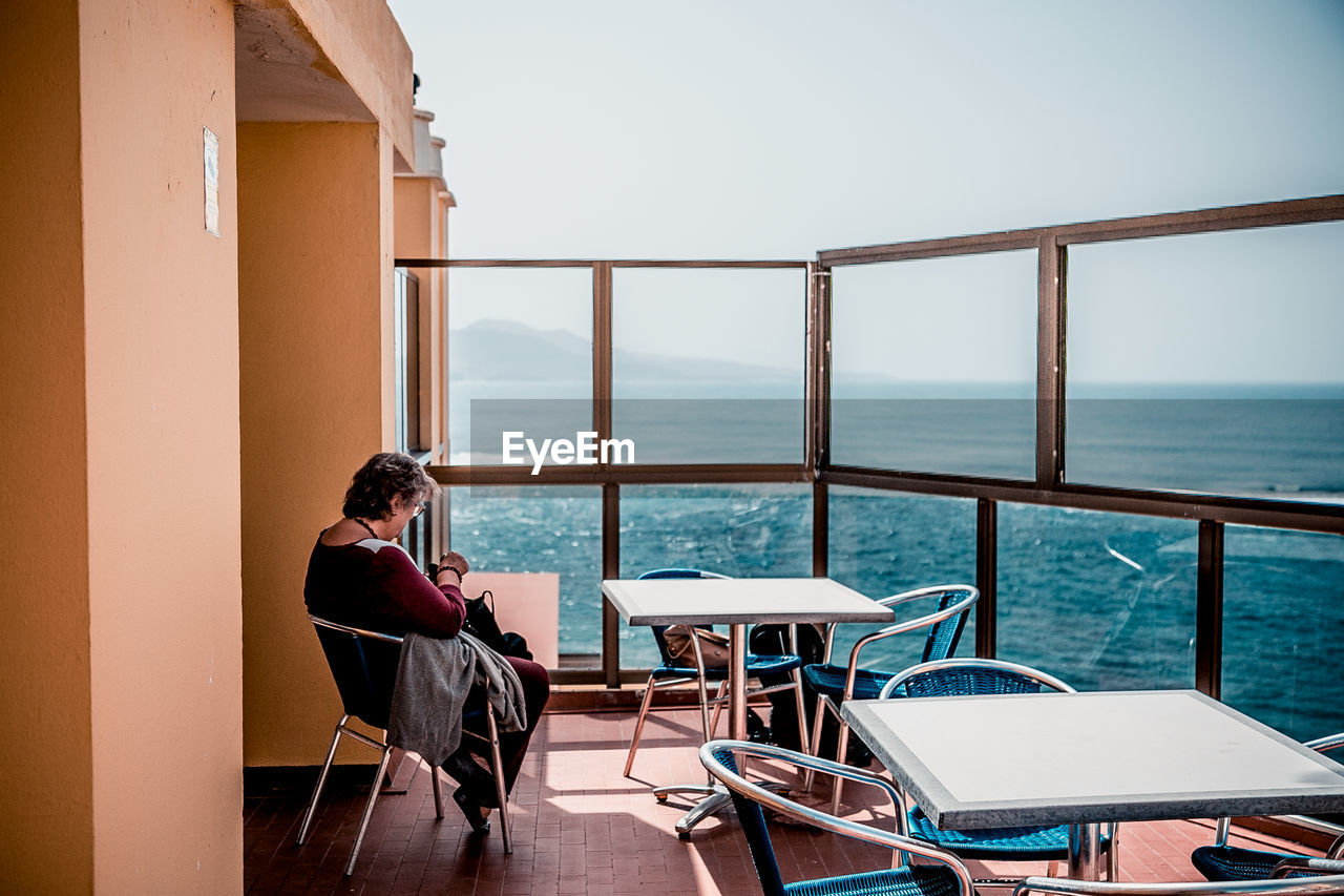 Woman Sitting On Terrace By Sea Against Sky
