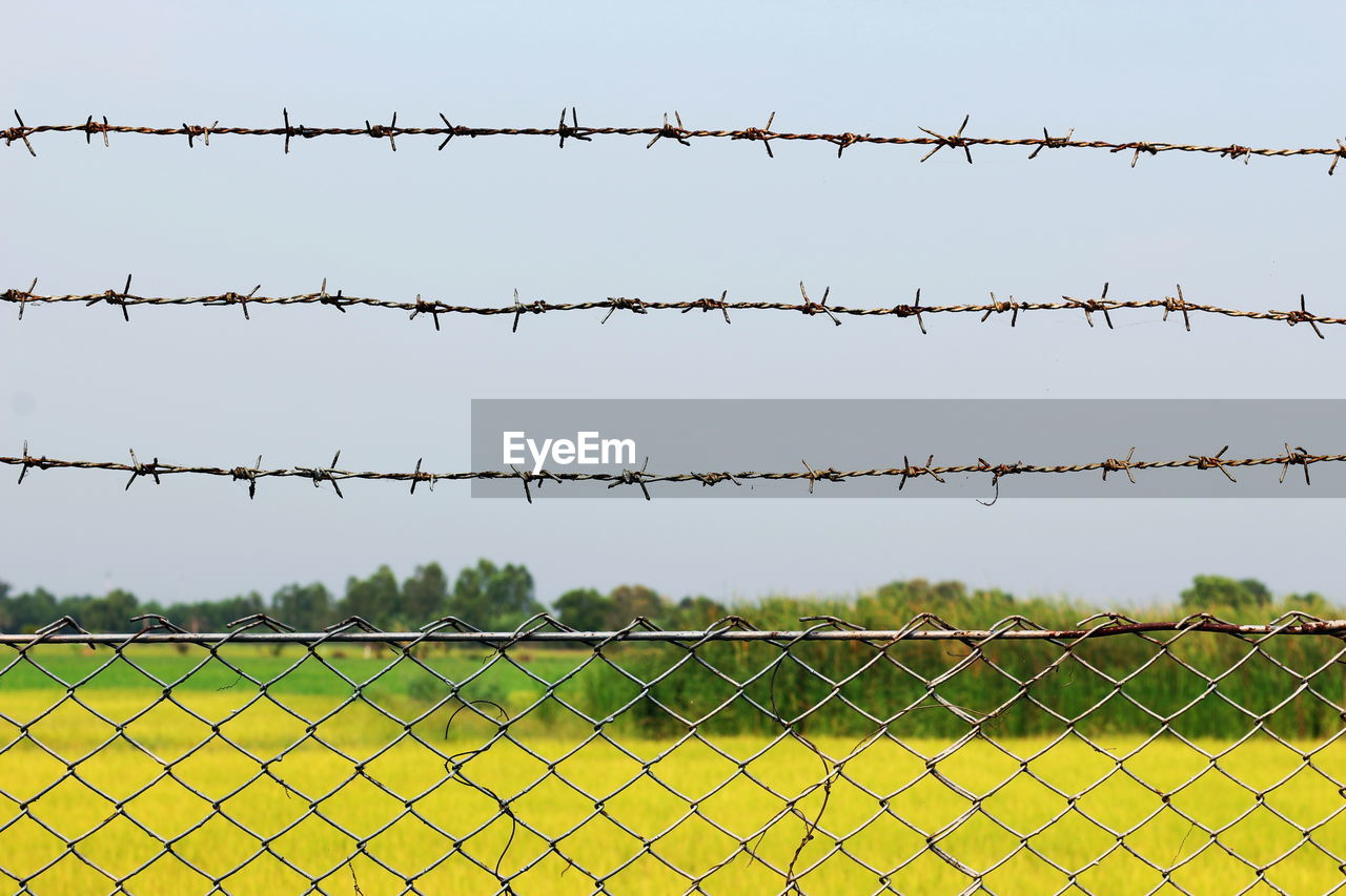 Barbed wire fence on field against clear sky