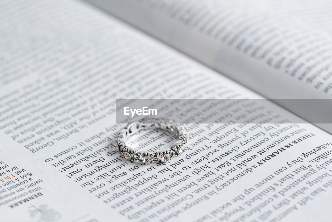 text, no people, publication, close-up, book, paper, selective focus, still life, full frame, newspaper, communication, indoors, western script, wealth, backgrounds, high angle view, ring, page, education, jewelry