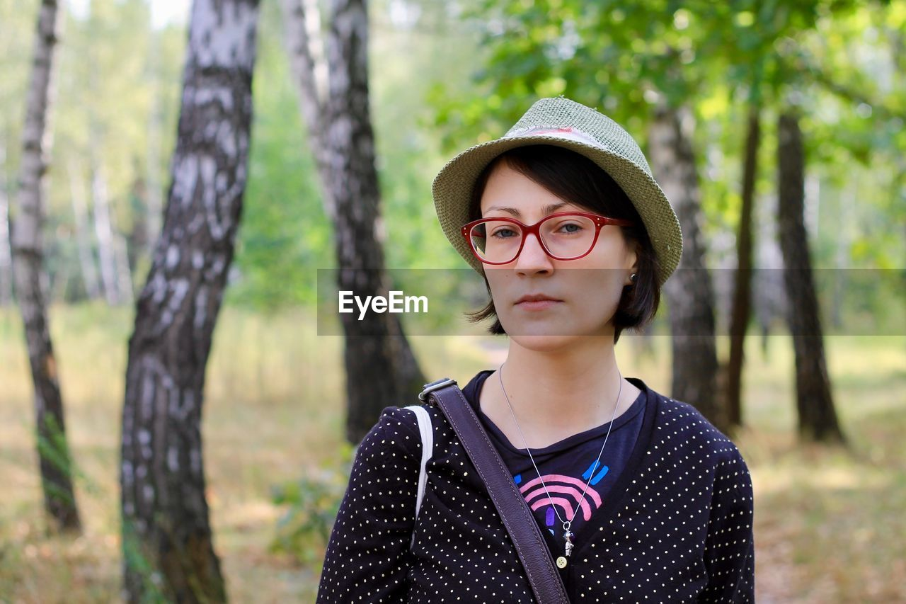 tree, portrait, glasses, one person, eyeglasses, front view, forest, plant, real people, focus on foreground, trunk, looking at camera, tree trunk, headshot, leisure activity, land, lifestyles, day, outdoors, teenager