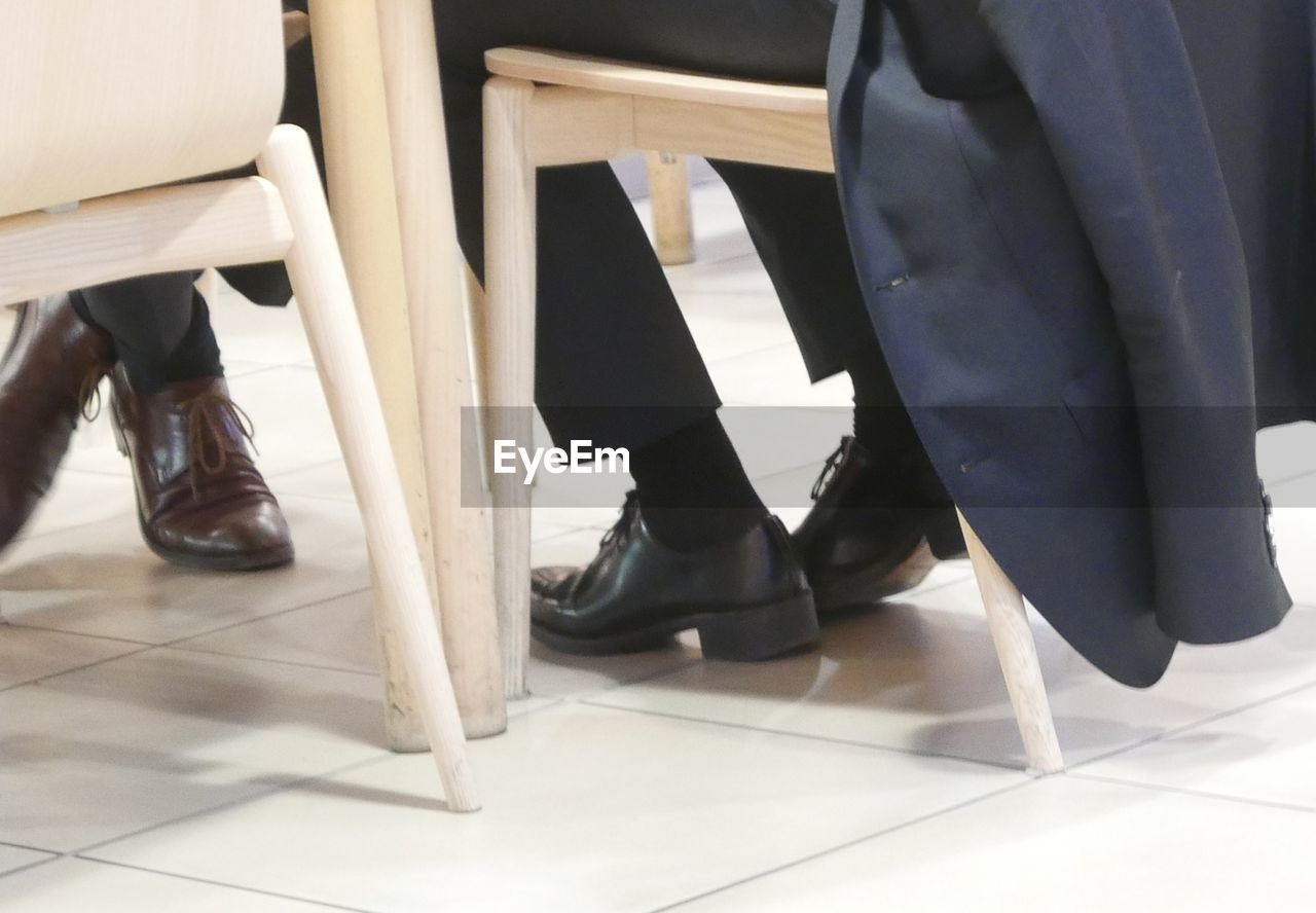 Low Section Of Men Wearing Shoes Sitting On Chair