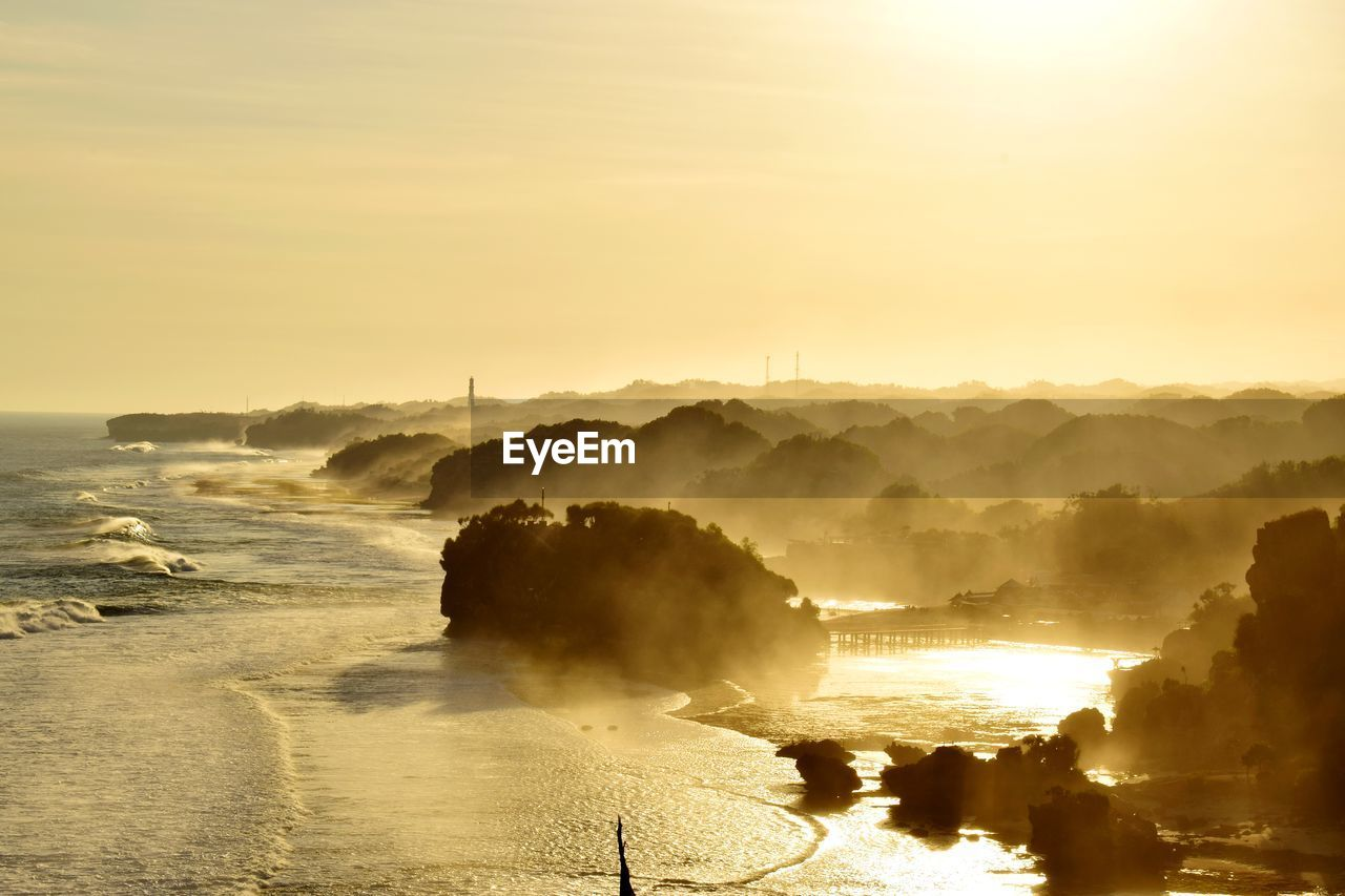 sky, water, beauty in nature, scenics - nature, sunset, idyllic, tranquil scene, nature, tranquility, sea, non-urban scene, orange color, no people, beach, fog, outdoors, land, sunlight