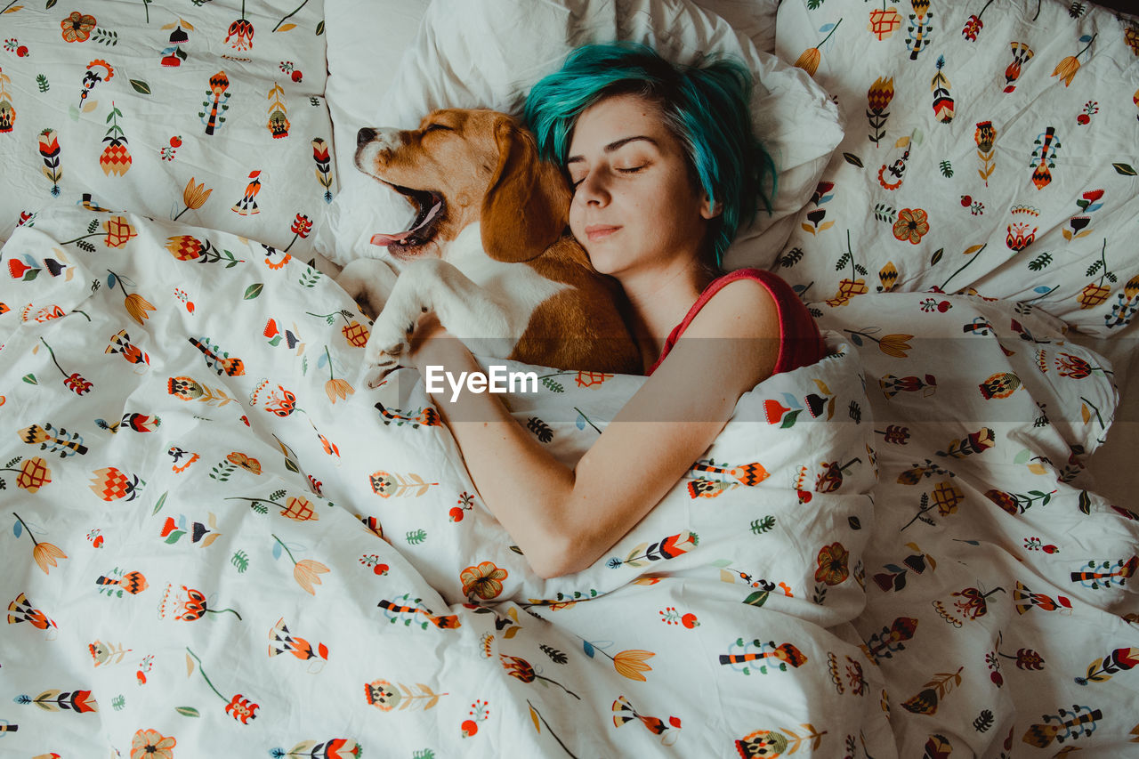 High angle view of woman sleeping with dog on bed