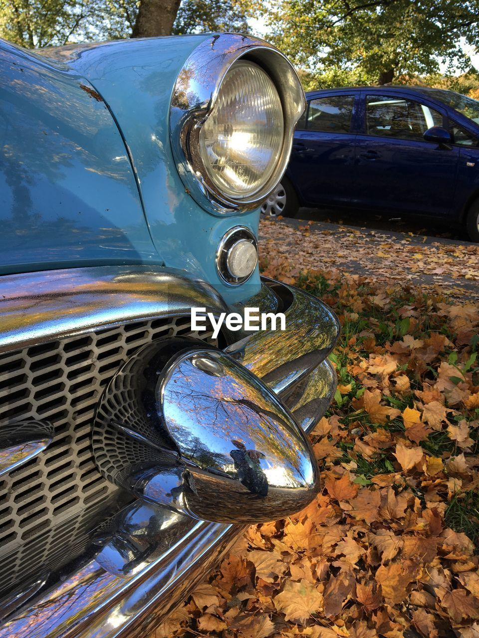 car, motor vehicle, mode of transportation, land vehicle, transportation, headlight, metal, day, vintage car, stationary, retro styled, outdoors, no people, nature, tree, reflection, vehicle hood, chrome, close-up, silver colored