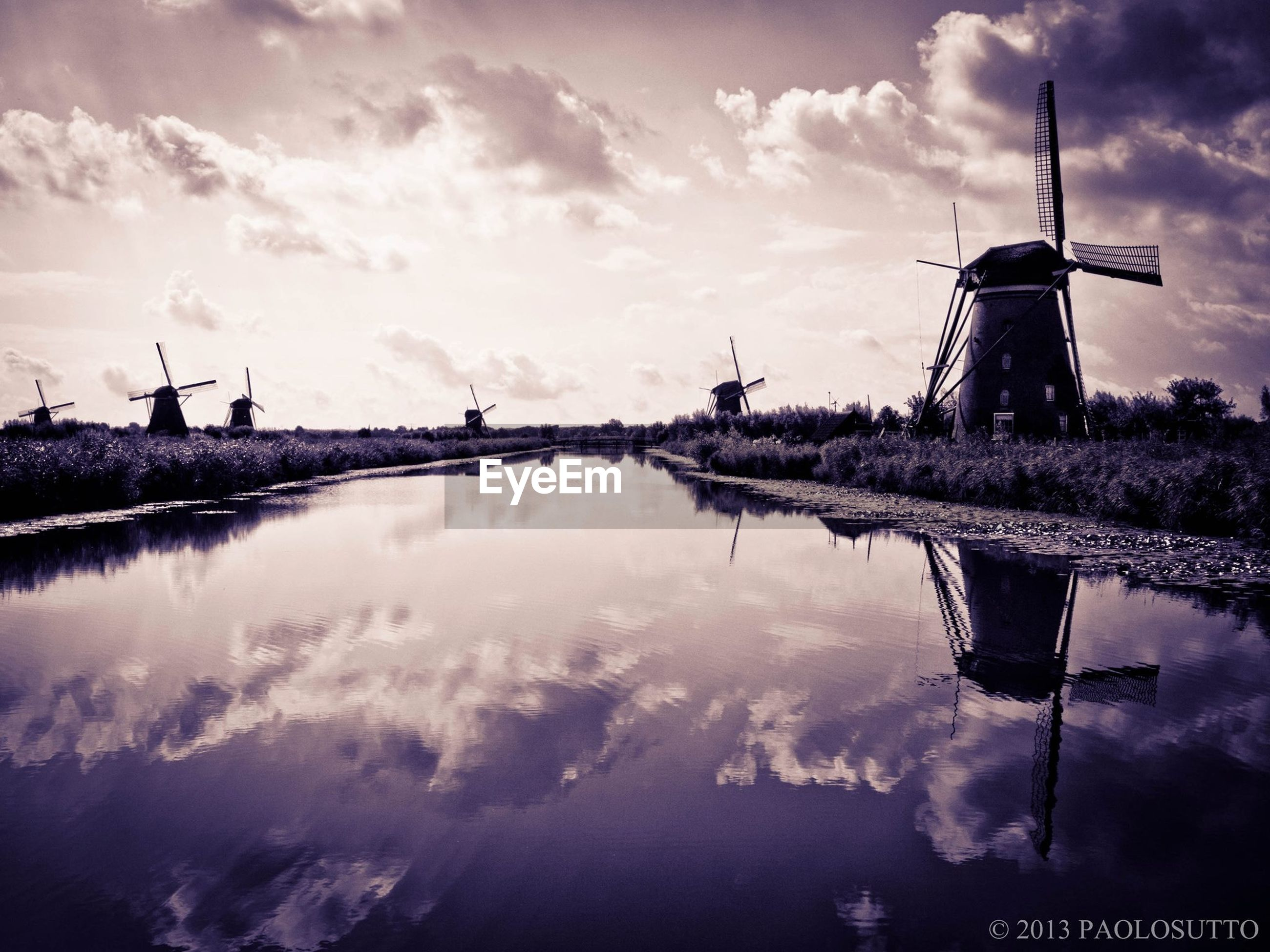 water, sky, cloud - sky, reflection, cloudy, built structure, lake, architecture, tranquility, nature, standing water, cloud, weather, tranquil scene, scenics, building exterior, river, waterfront, windmill, beauty in nature