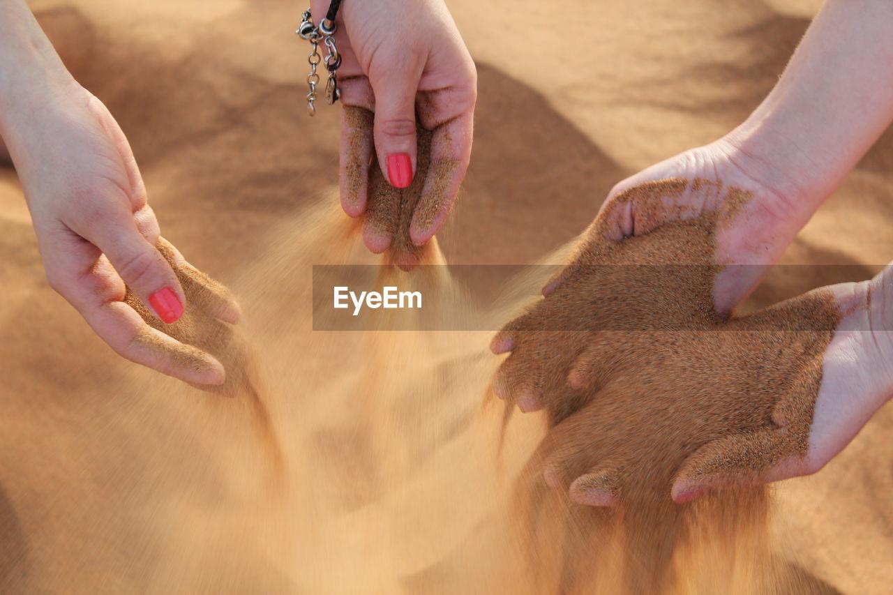 Women Sifting Sand Through Their Fingers On The Beach