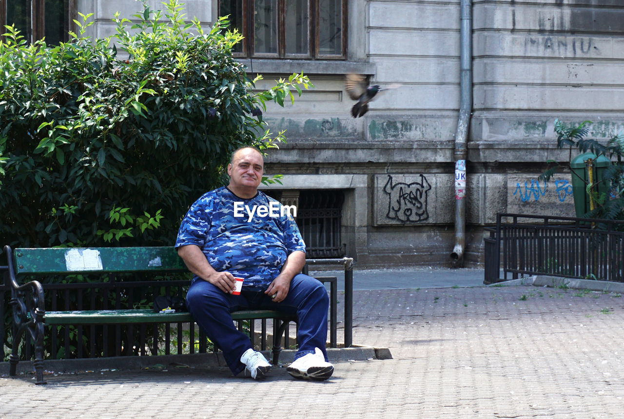 one person, sitting, seat, real people, full length, casual clothing, leisure activity, lifestyles, bench, front view, day, architecture, men, young adult, looking away, plant, building exterior, young men, outdoors, mature men, contemplation, park bench