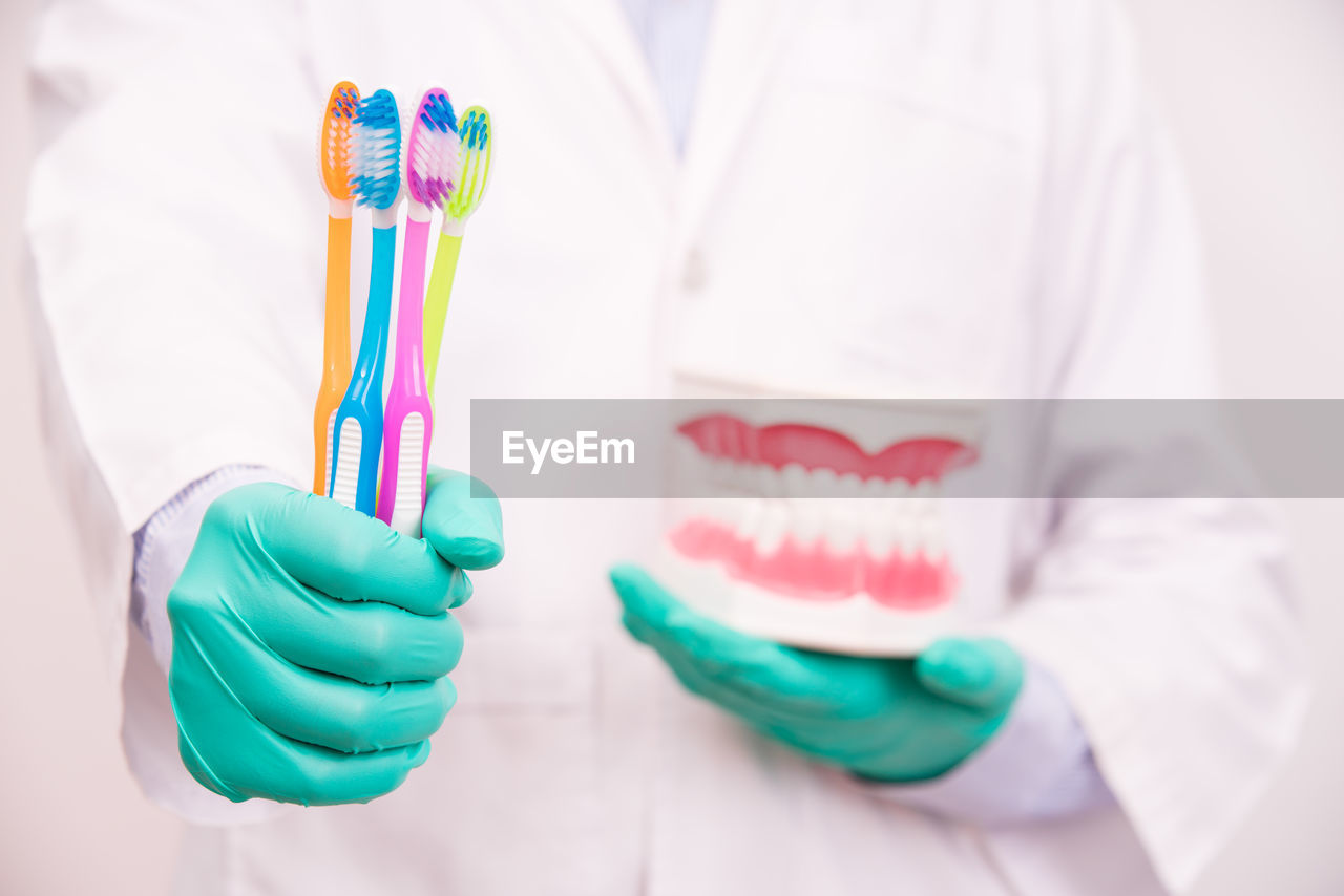 Midsection Of Dentist Holding Dentures And Toothbrushes