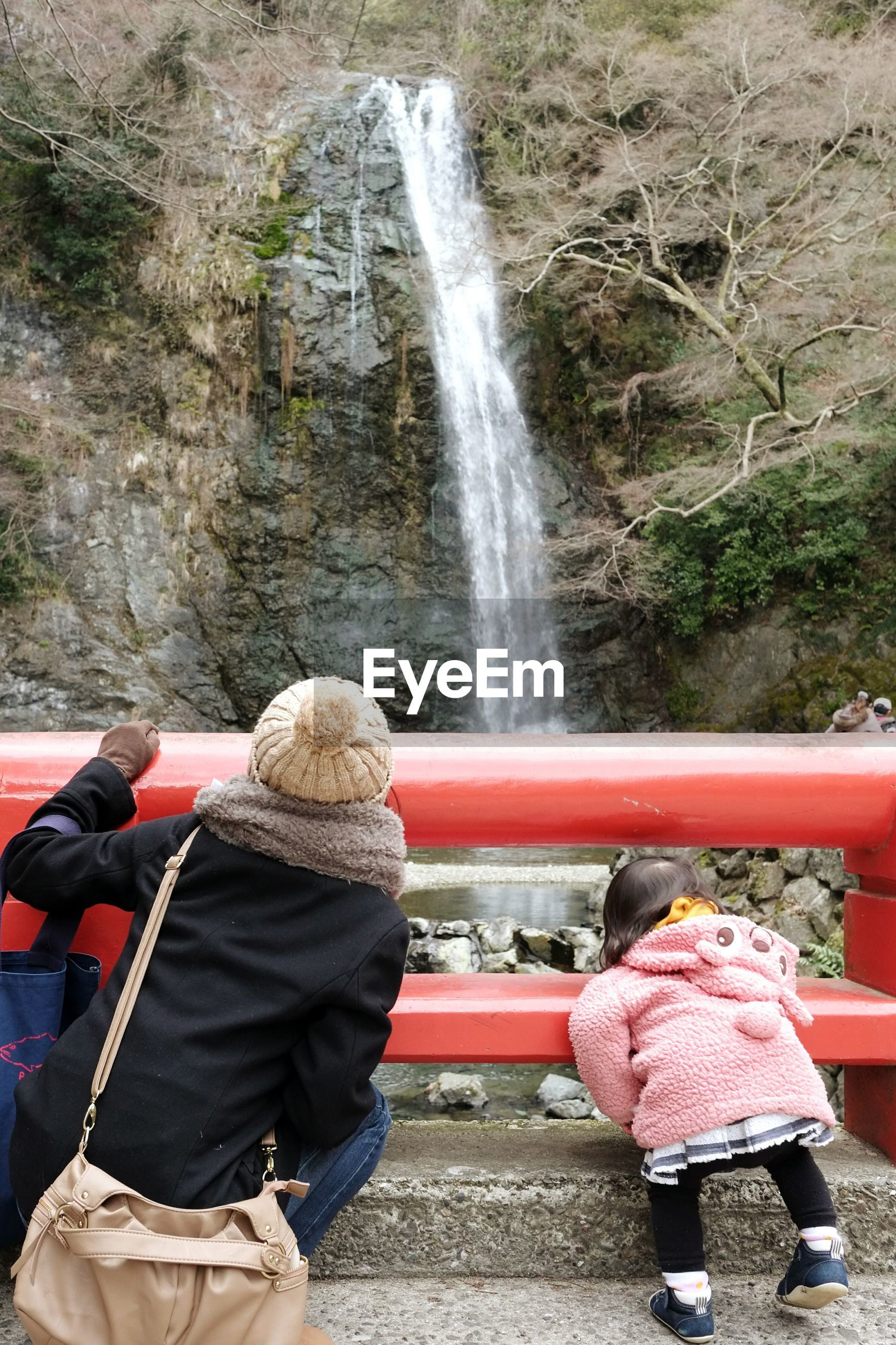 motion, waterfall, leisure activity, lifestyles, rear view, casual clothing, full length, person, tourism, flowing water, day, outdoors, flowing, beauty in nature, natural landmark, stone material, scenics