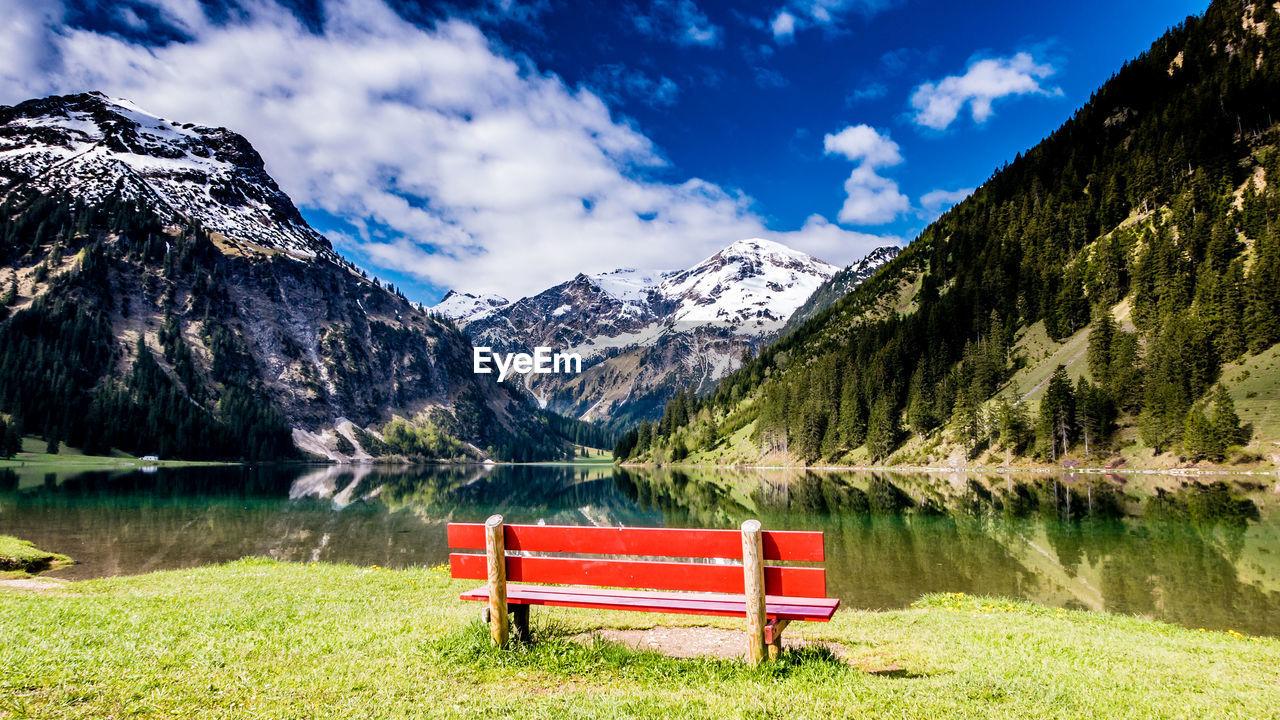Bench By Lake Against Mountain Range