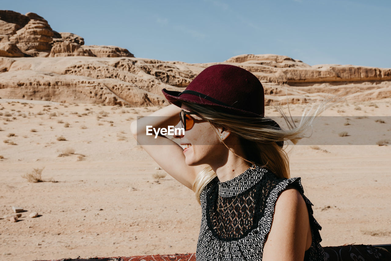 Smiling Woman Wearing Hat At Beach Against Sky