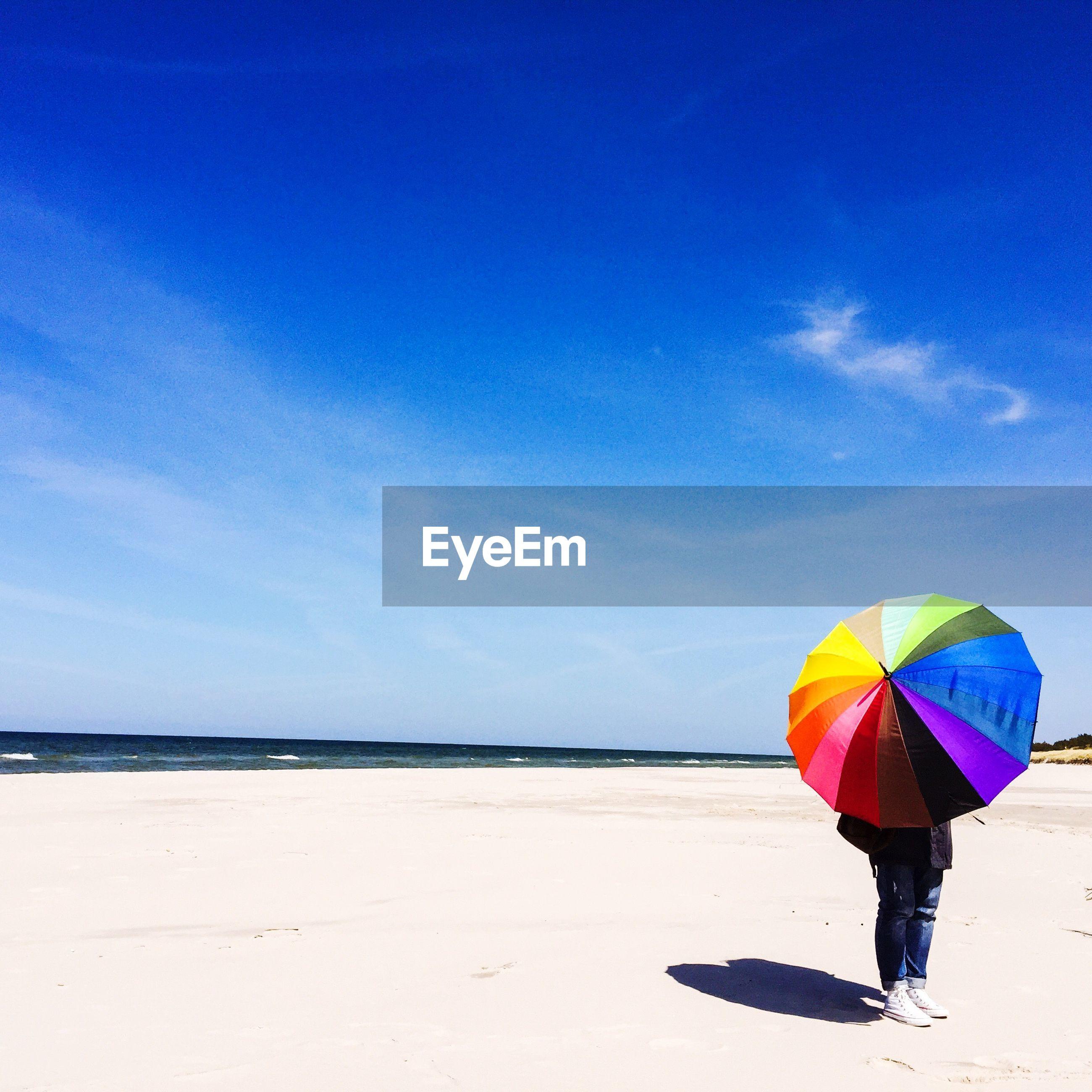 Person with multi colored umbrella standing on beach