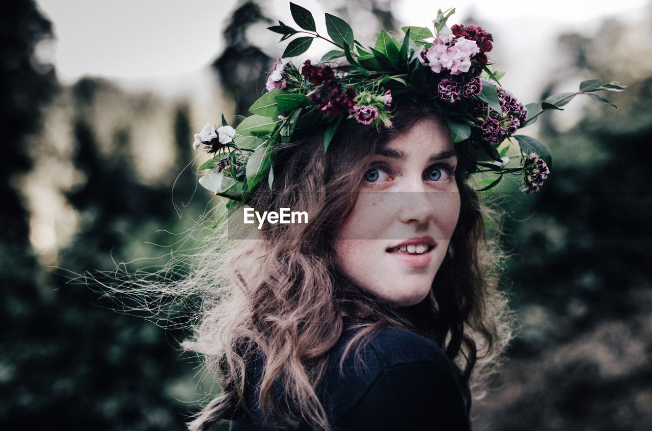 flower, real people, young adult, focus on foreground, one person, headshot, laurel wreath, young women, looking at camera, lifestyles, outdoors, front view, long hair, leisure activity, beautiful woman, portrait, wearing flowers, day, close-up, nature, crown, tree, people