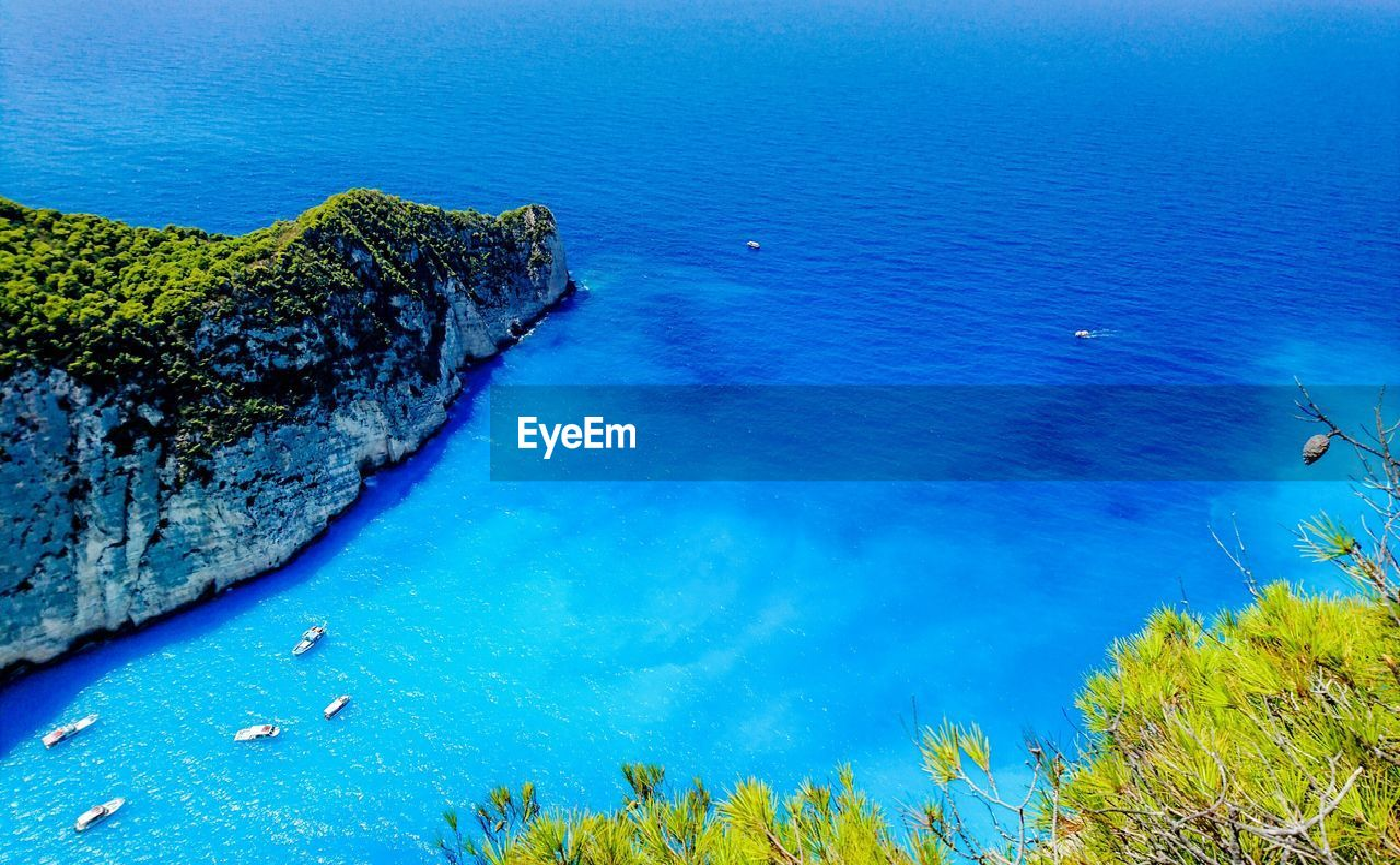 SEA BY ROCKS AGAINST BLUE SKY