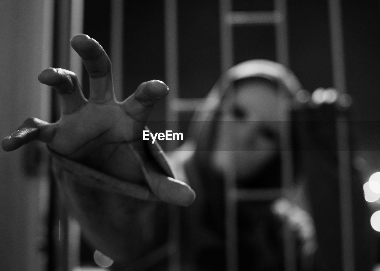 Close-Up Of Burglar Wearing Mask Peeking Through Window