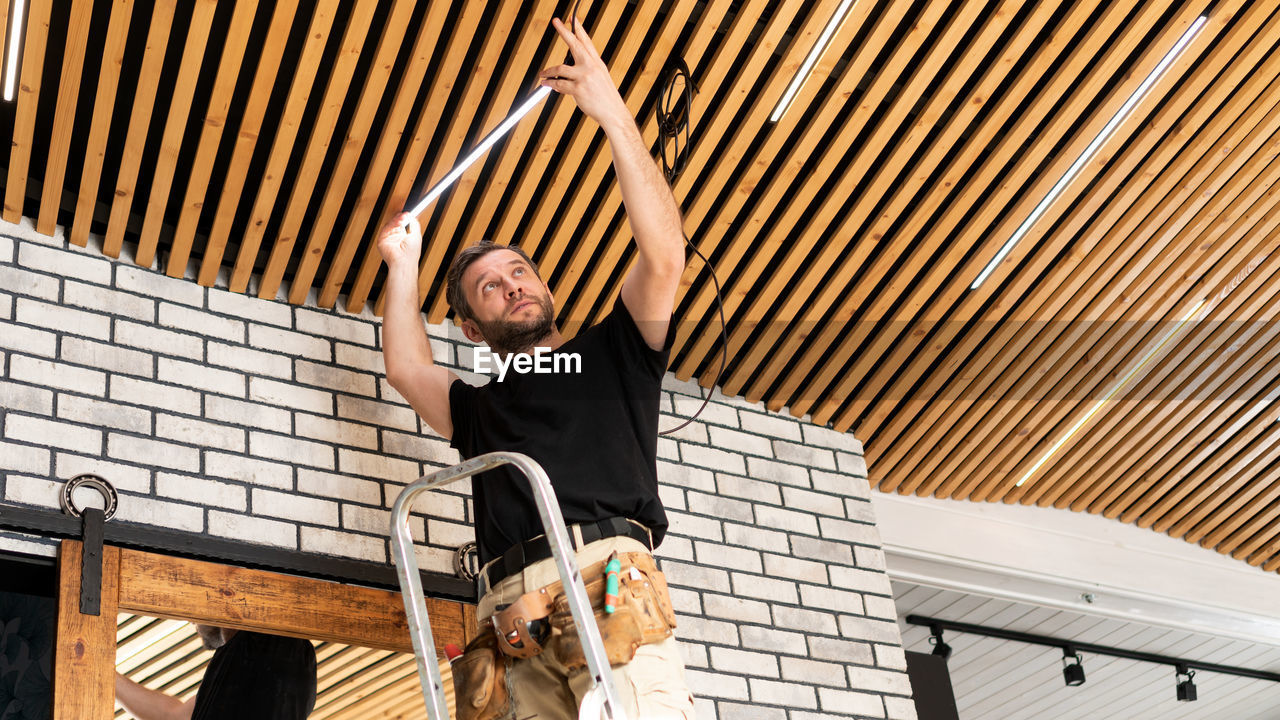 Low angle view of man repairing ceiling