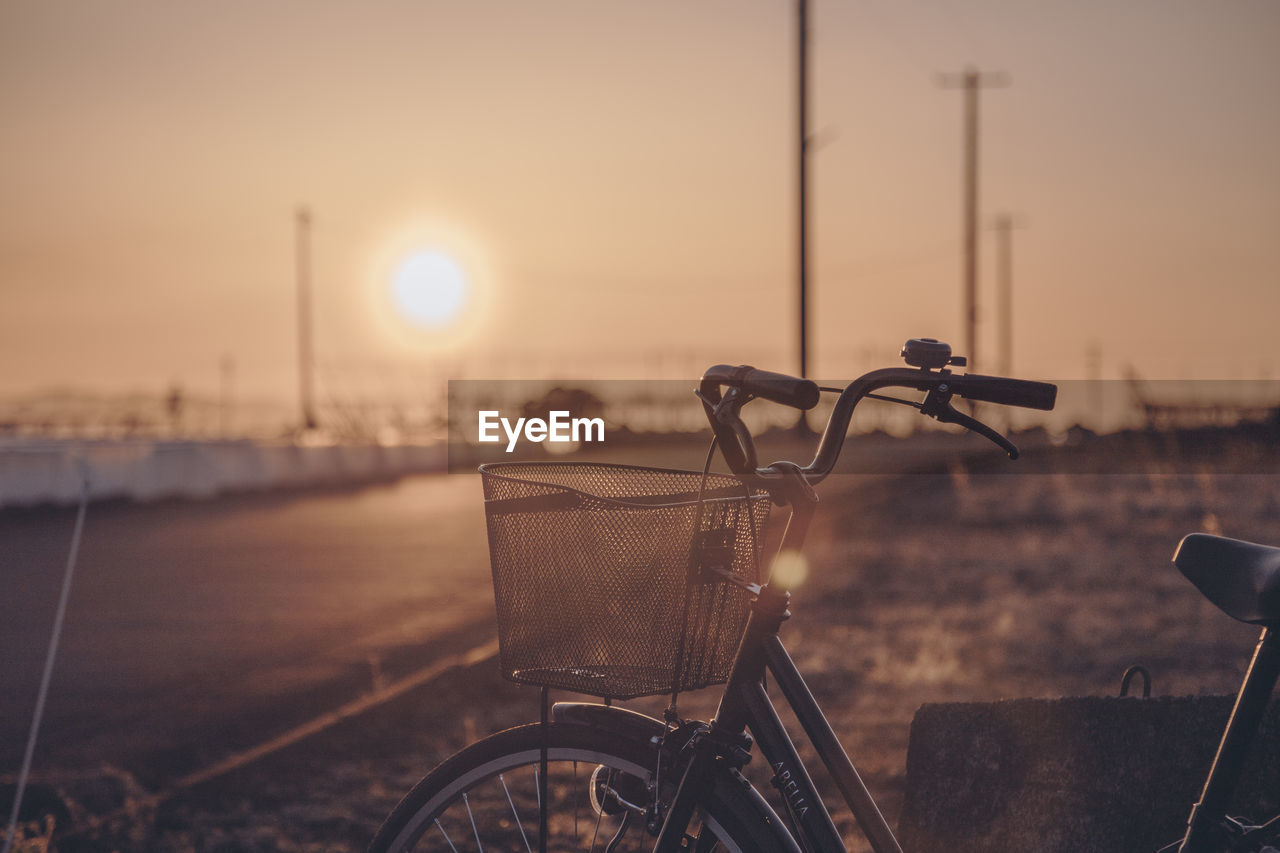 bicycle, transportation, sunset, mode of transportation, sky, land vehicle, focus on foreground, stationary, city, basket, nature, bicycle basket, no people, architecture, outdoors, water, street, travel, sunlight, wheel