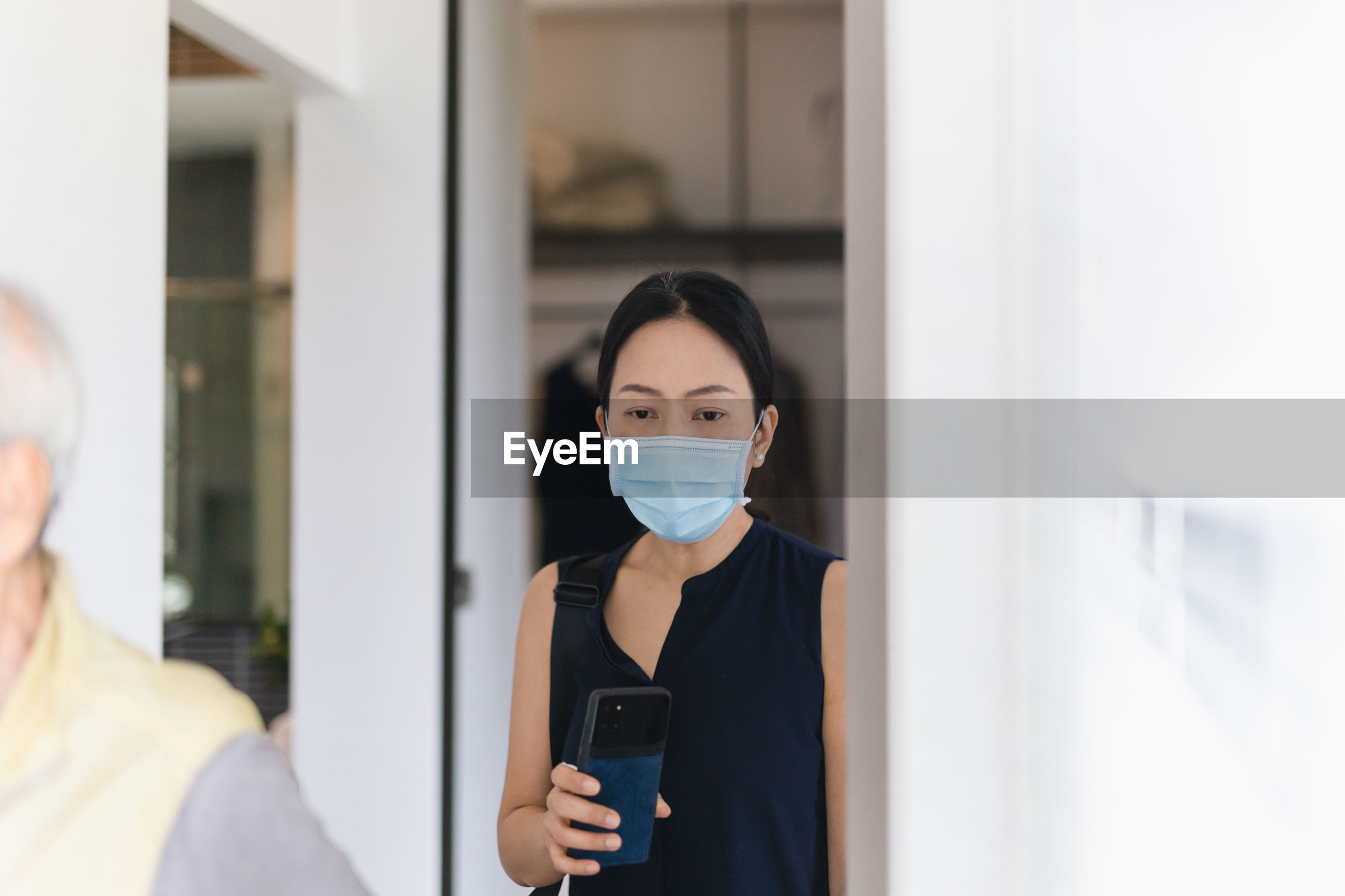 Portrait of woman in medical mask using cell phone