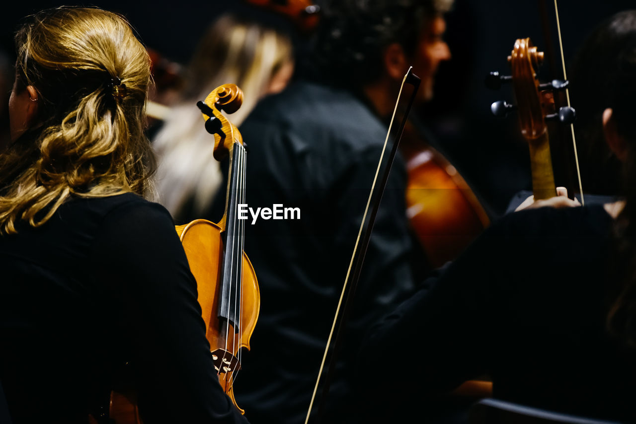 Woman holding violin while sitting in music concert