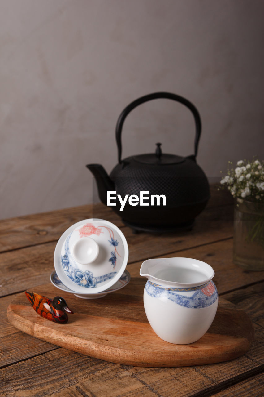 CUP OF TEA ON TABLE AGAINST WALL
