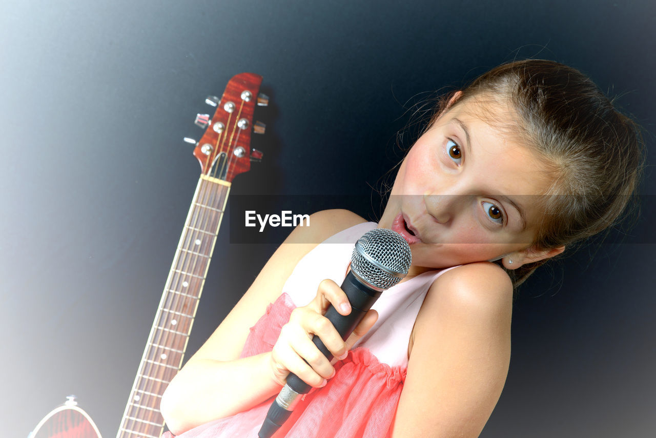 Portrait Of Girl Singing Against Black Background