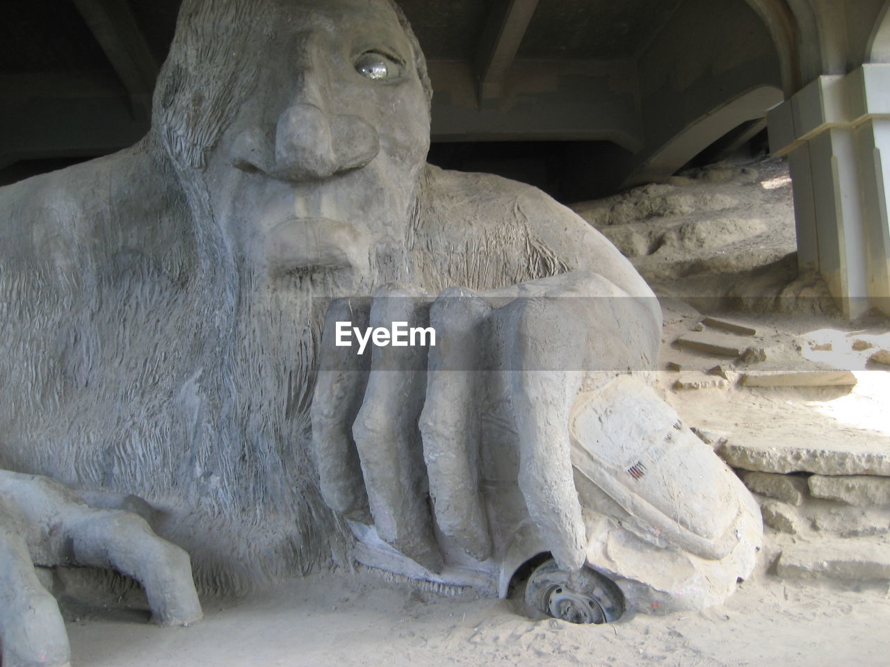Old white sculpture below bridge