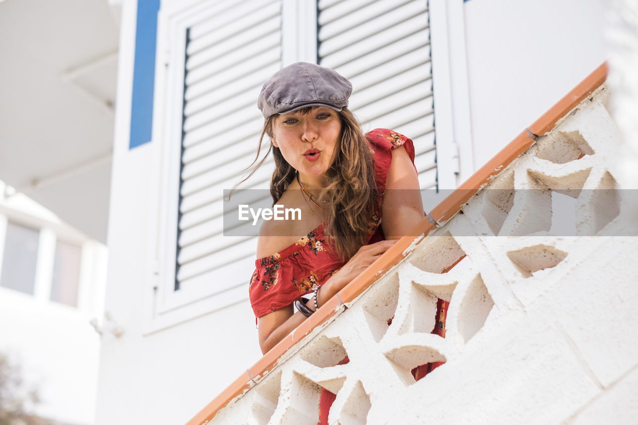 Low angle portrait of beautiful woman standing by railing on steps