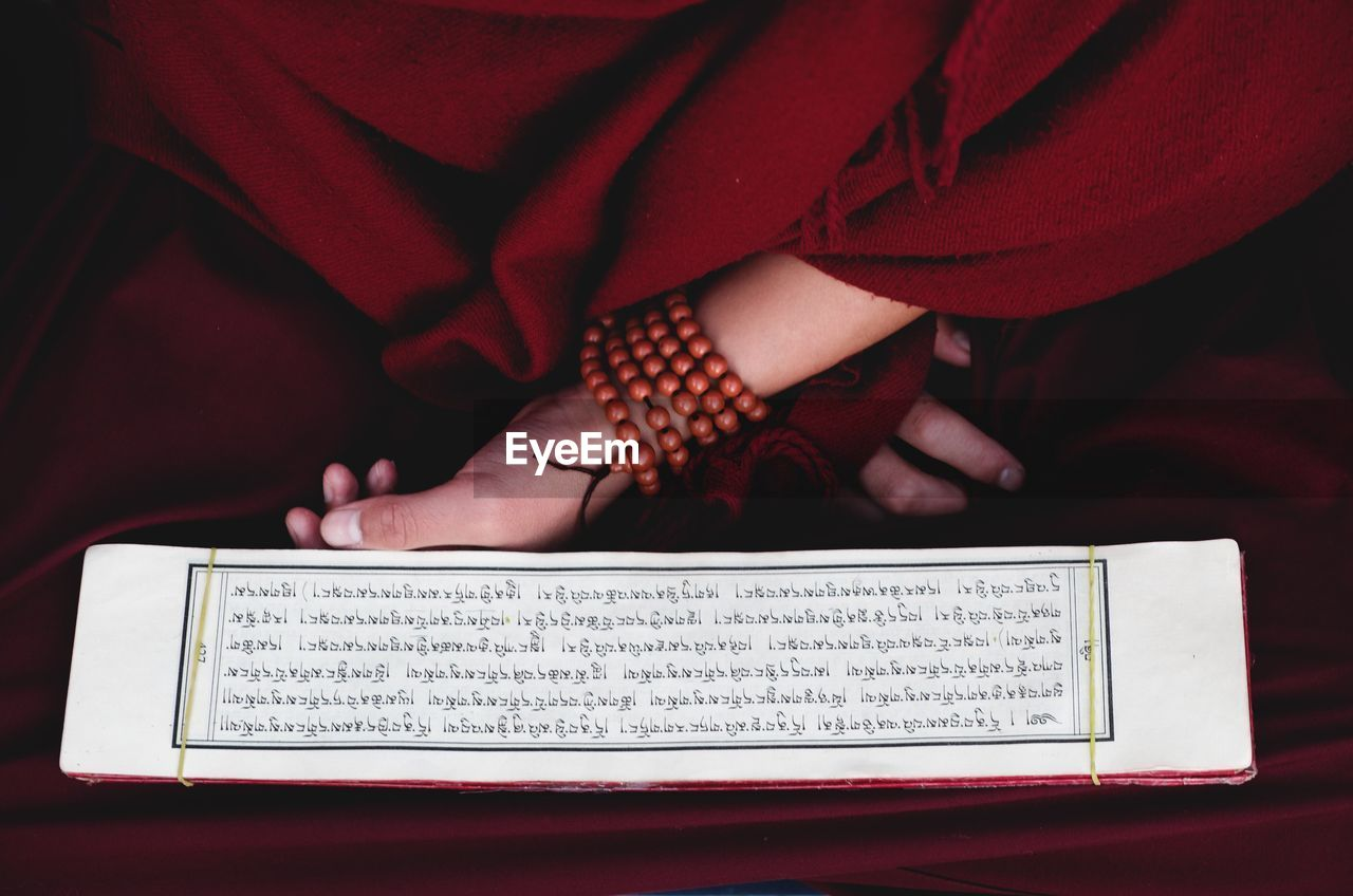 Midsection of monk reading text on paper