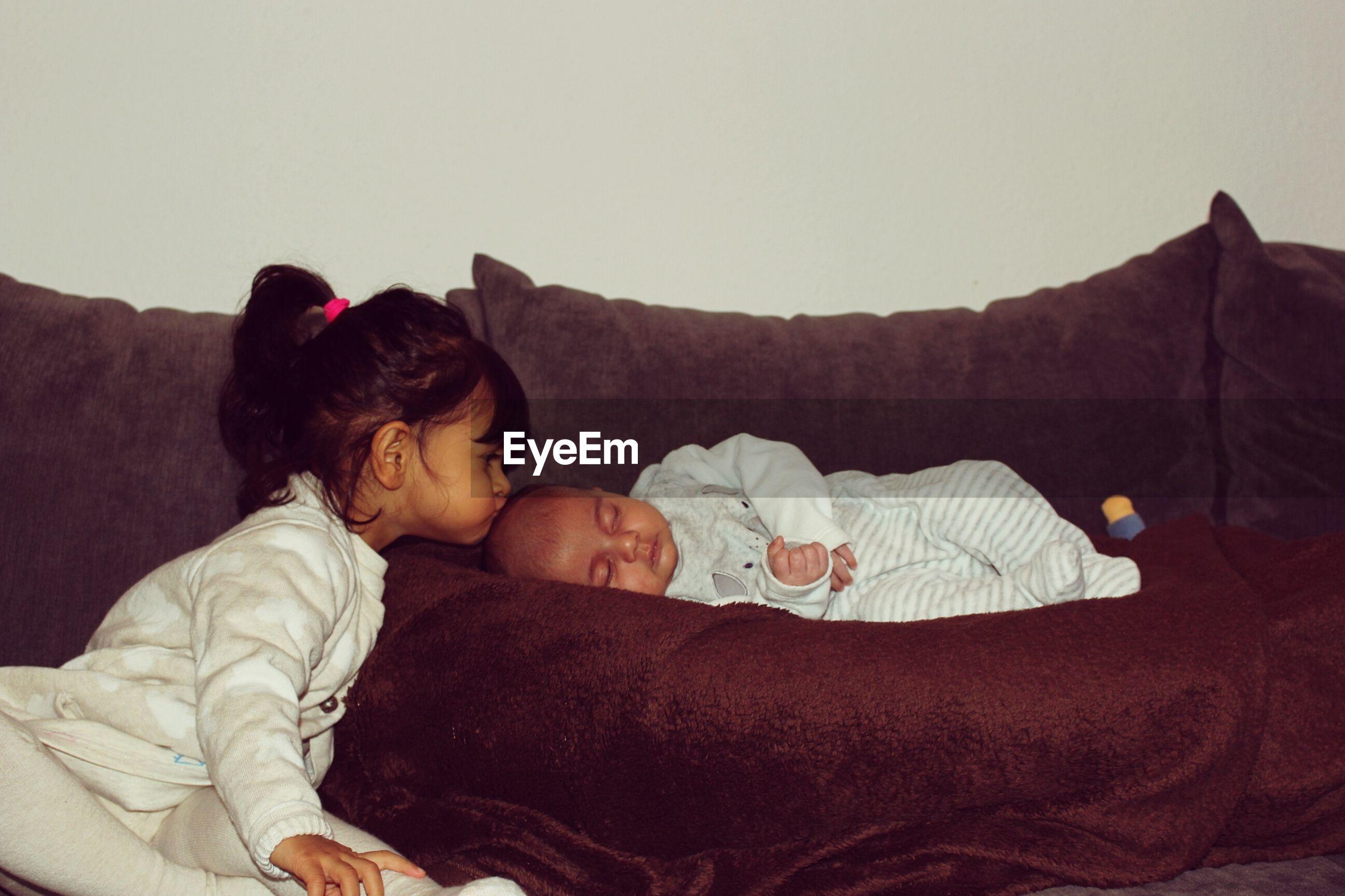 Sister kissing sleeping brother on sofa at home
