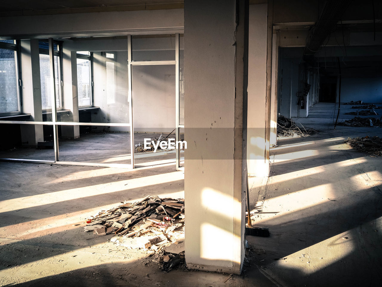 architecture, sunlight, built structure, no people, day, architectural column, nature, shadow, outdoors, abandoned, window, building, damaged, transportation, obsolete, entrance, parking lot, ruined