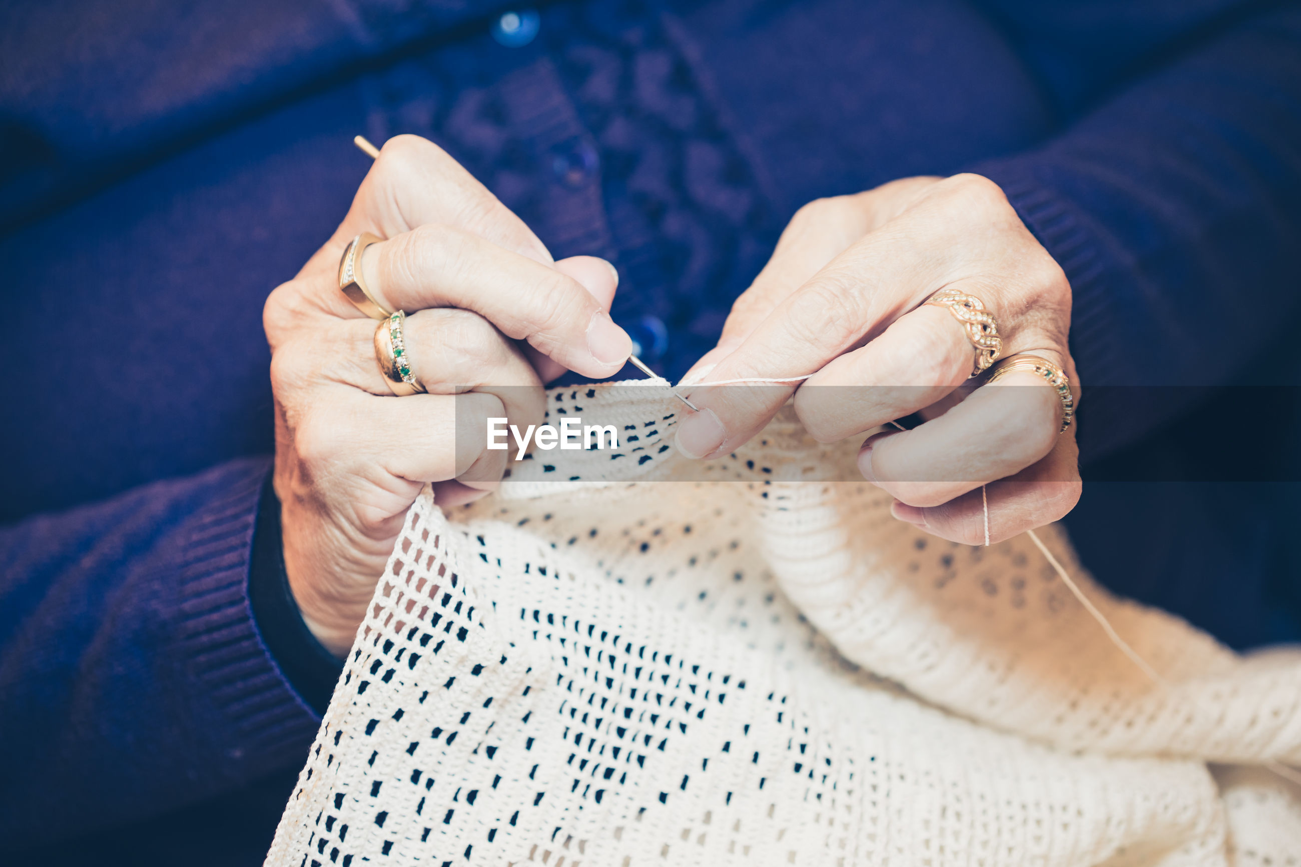 Midsection of woman knitting textile