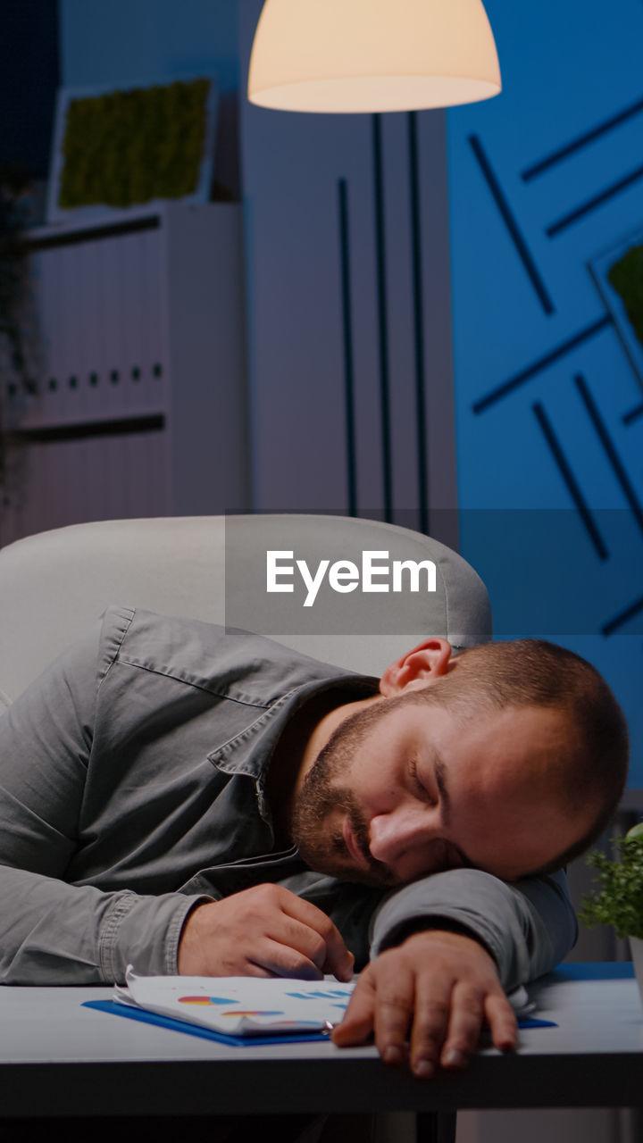 FULL LENGTH OF MAN SLEEPING ON TABLE