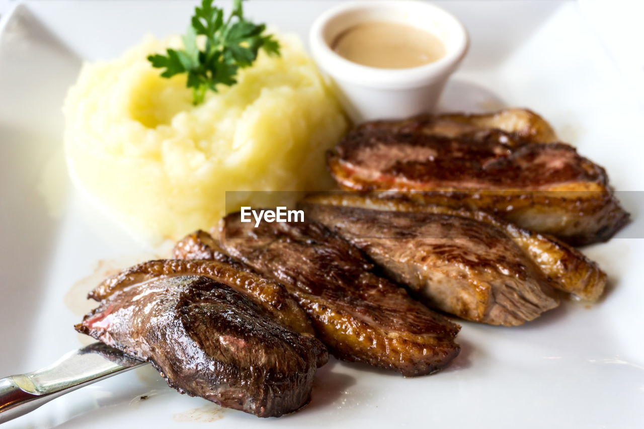 Close-up of steak and mashed potatoes served in plate