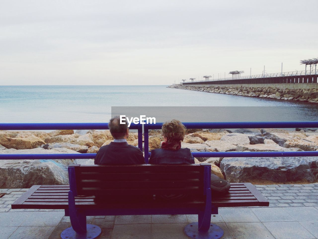 Rear View Of Couple Sitting On Bench At Beach