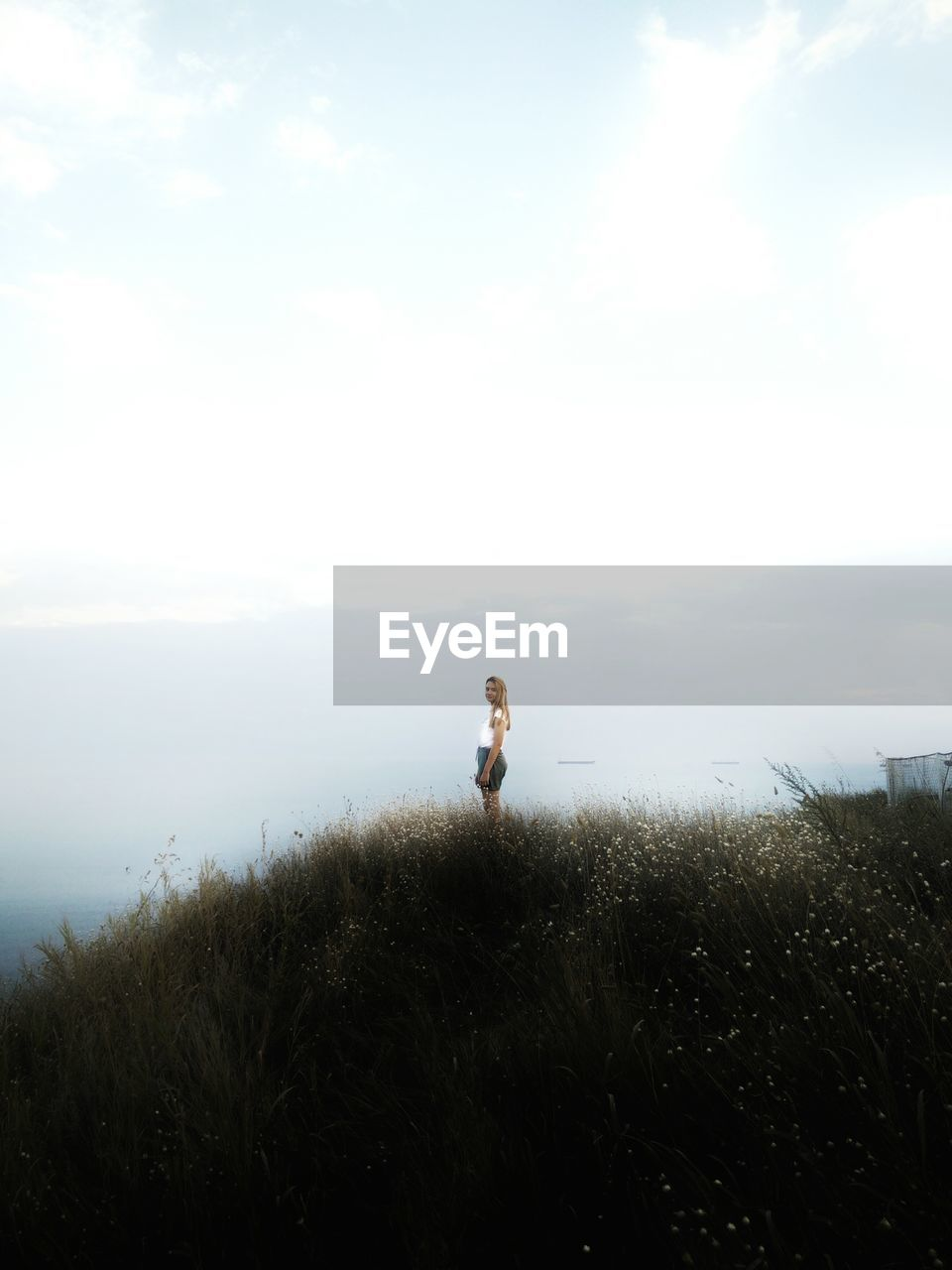 Young Woman Standing On Mountain Against Clear Sky