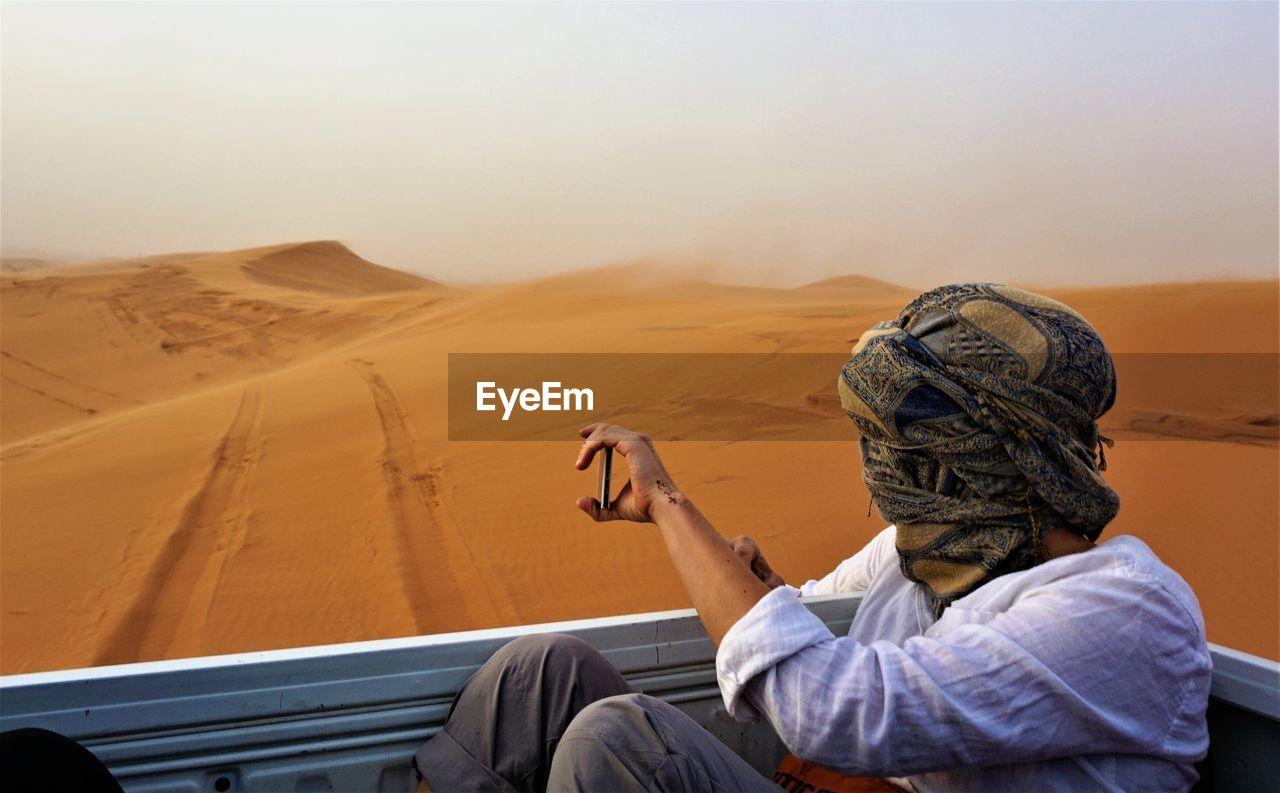 Man Sitting In Vehicle At Desert Against Sky