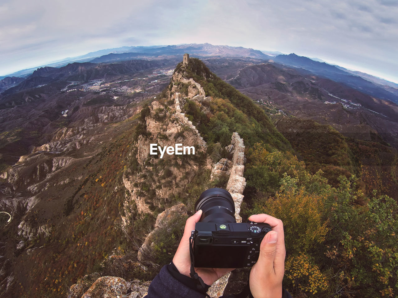 Cropped image of man photographing mountain with camera against sky