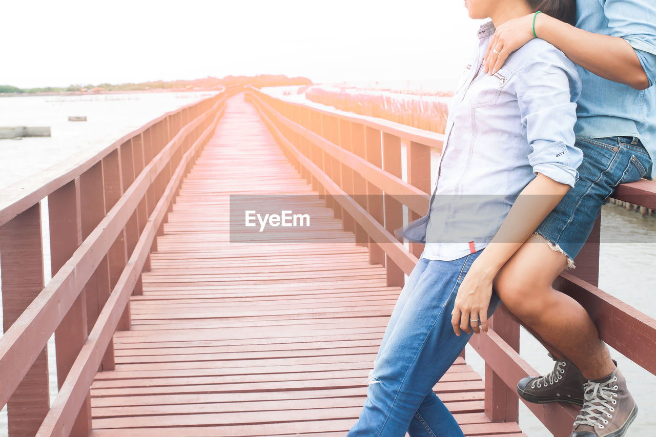 Side View Of Couple At Footbridge