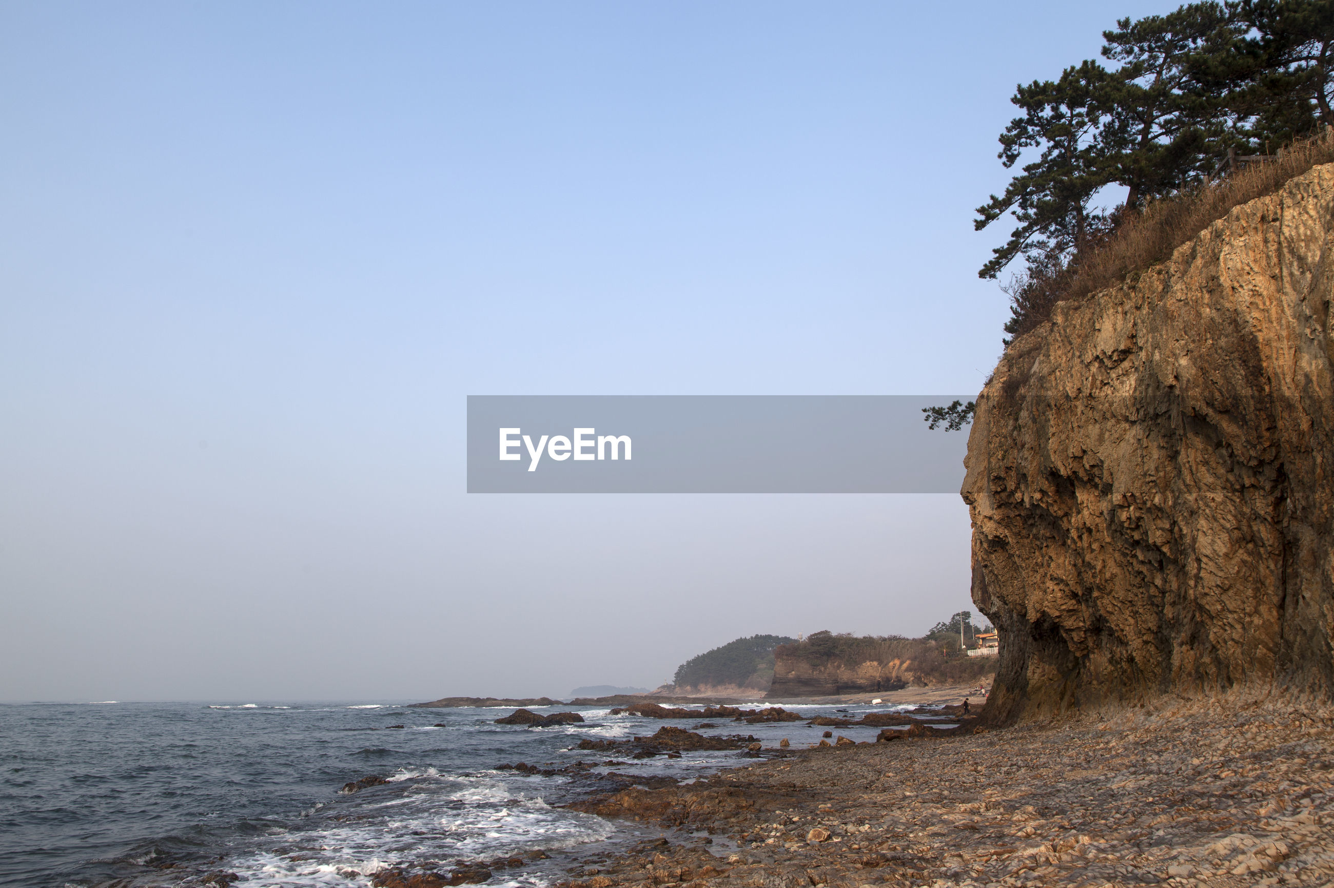 Scenic view cliff at gyeokpo beach against clear sky