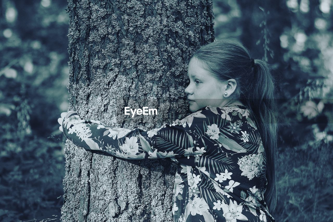 tree trunk, tree, childhood, one person, forest, leisure activity, real people, outdoors, day, hugging, nature, focus on foreground, holding, playing, embracing, girls, side view, happiness, smiling, tree stump, lifestyles, woodpecker, animal themes, young adult, people