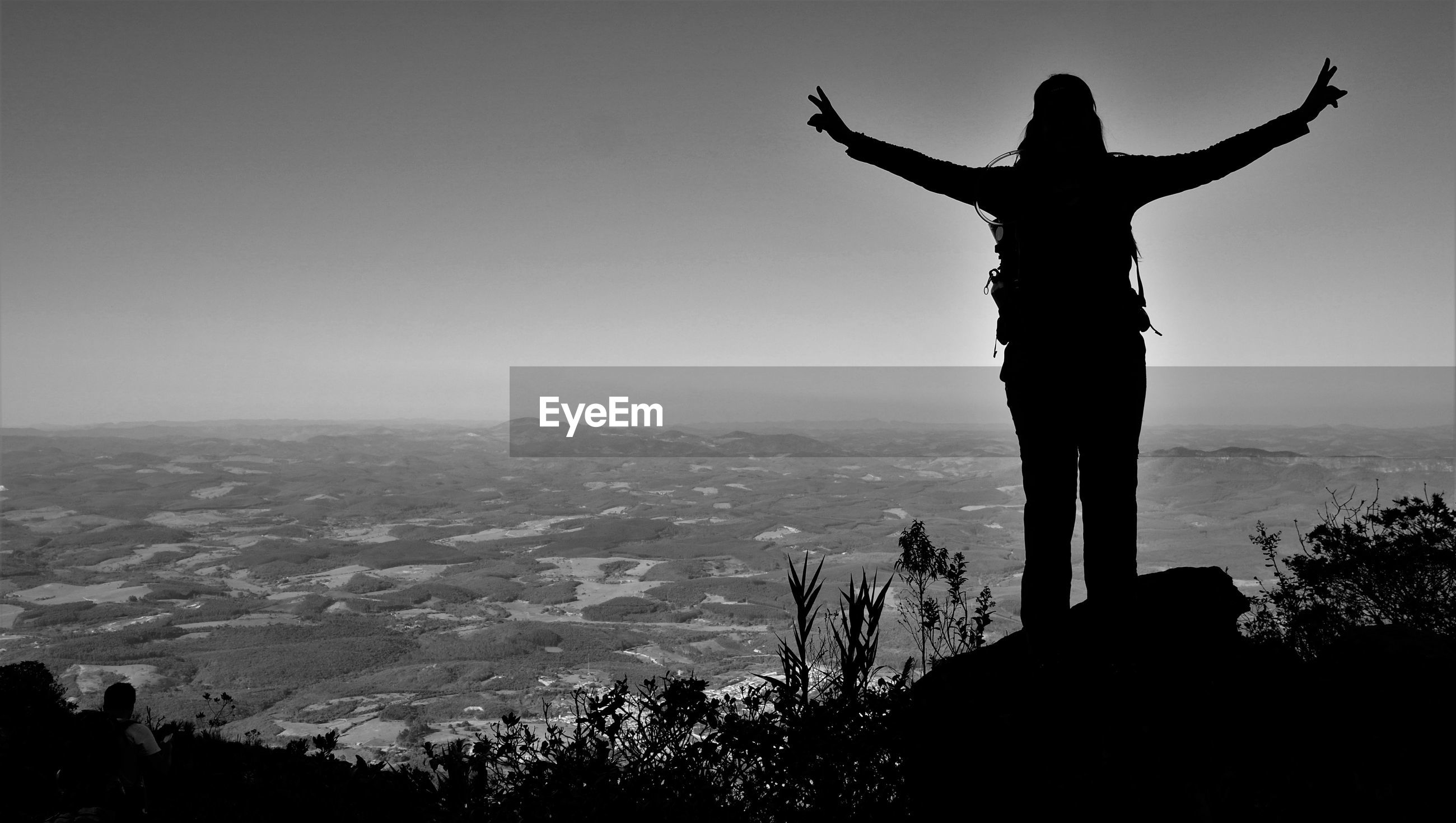 Silhouette person with backpack standing with arms outstretched on mountain against sky