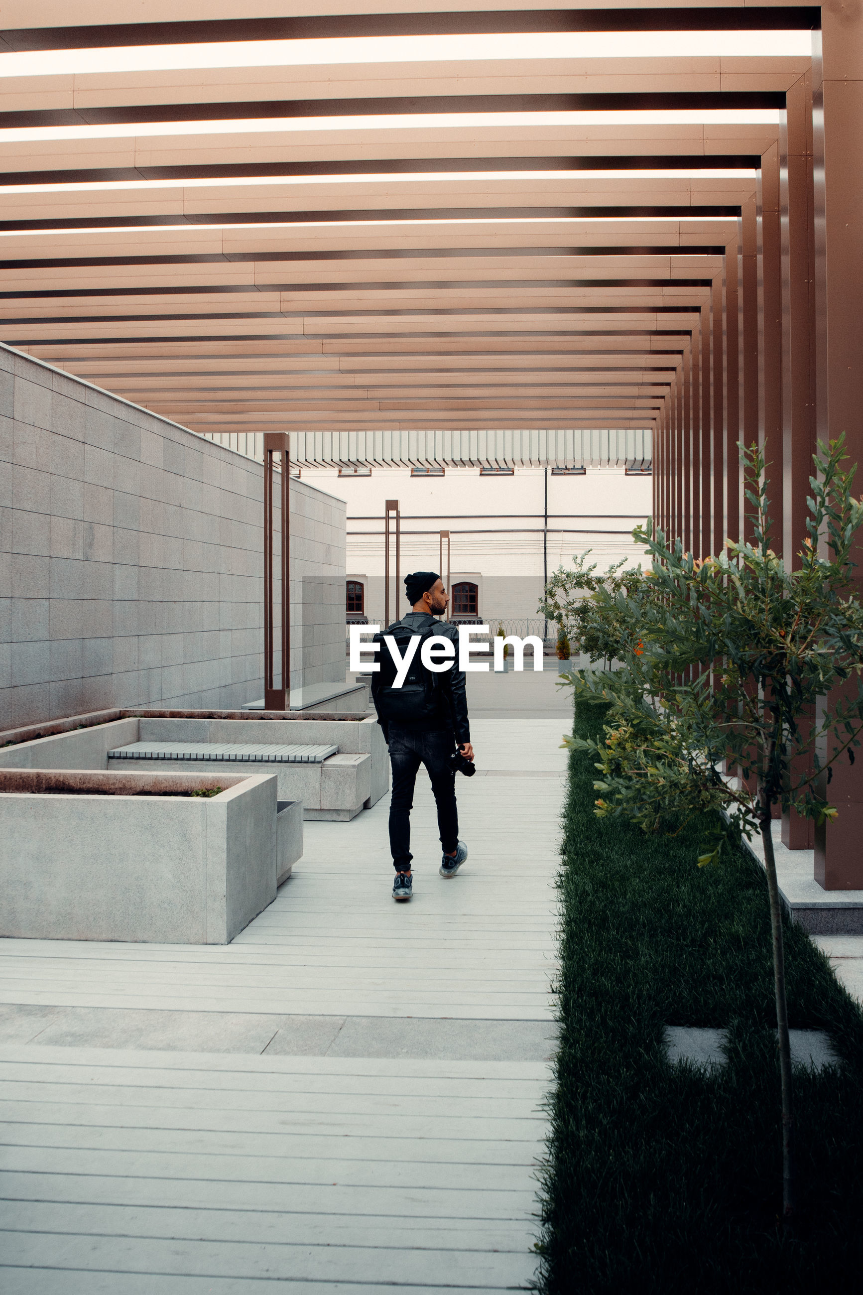 FULL LENGTH REAR VIEW OF MAN WALKING ON FOOTPATH