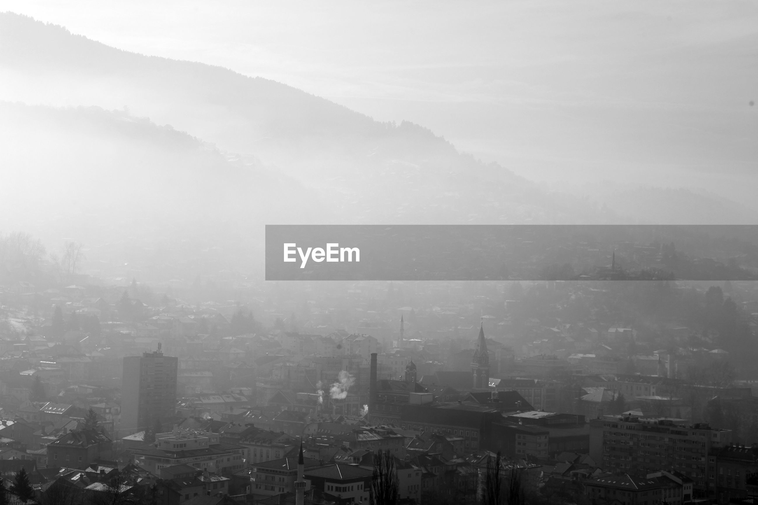 HIGH ANGLE VIEW OF BUILDINGS IN CITY DURING FOGGY WEATHER