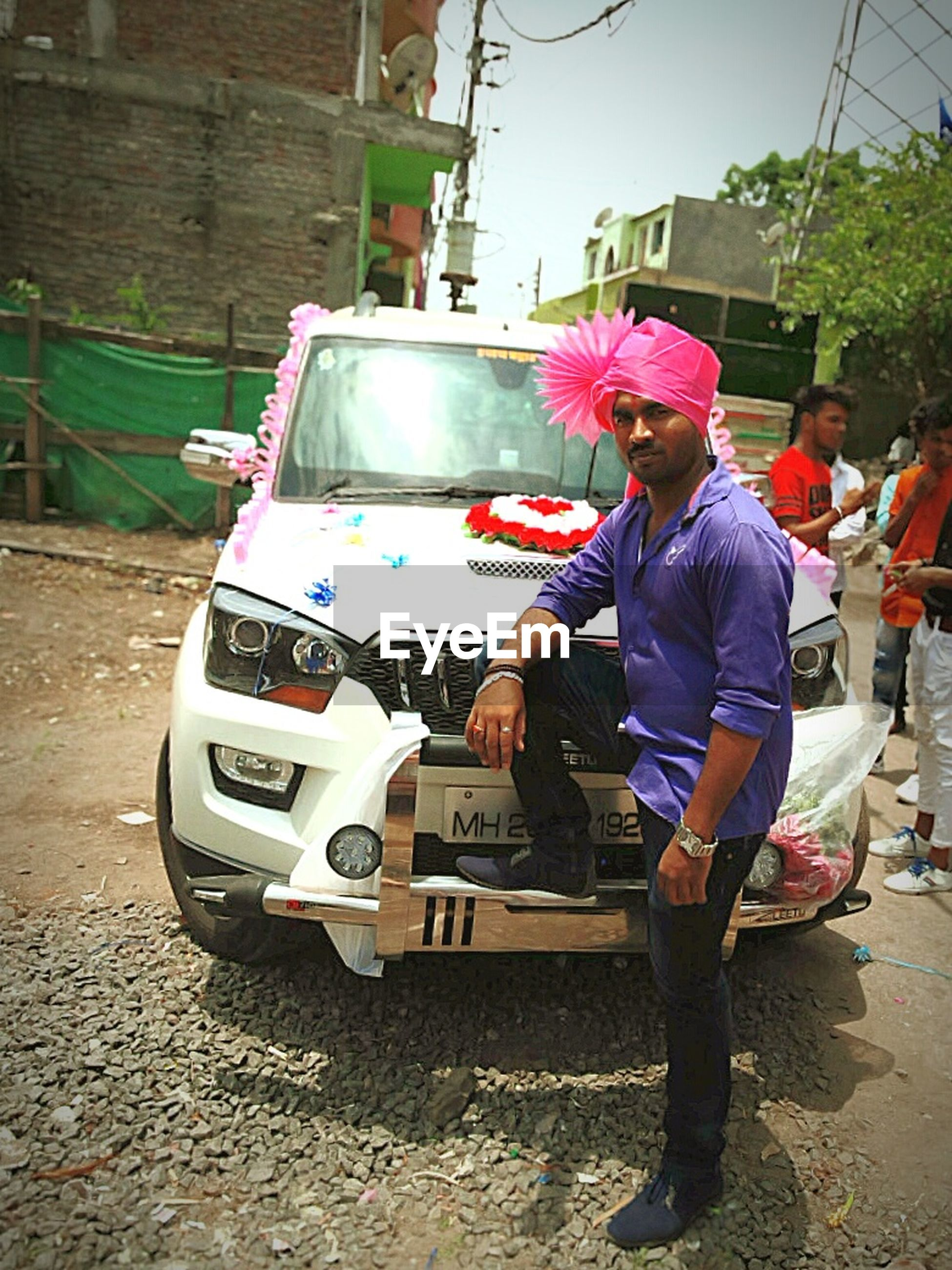 car, land vehicle, mode of transport, real people, transportation, standing, lifestyles, day, full length, one person, cap, outdoors, turban, men, adult, adults only, people