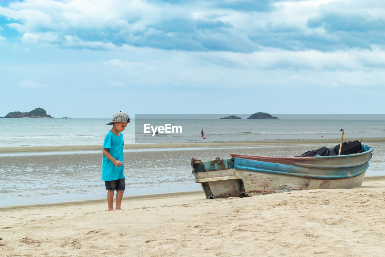 beach, sea, water, land, sky, sand, cloud - sky, full length, one person, nature, day, scenics - nature, beauty in nature, real people, casual clothing, rear view, nautical vessel, tranquil scene, horizon over water, outdoors