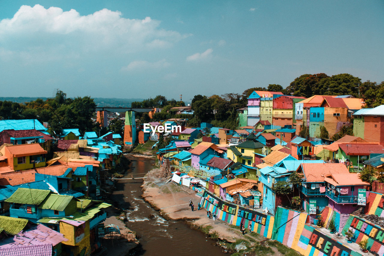High angle view of river amidst colorful houses against sky